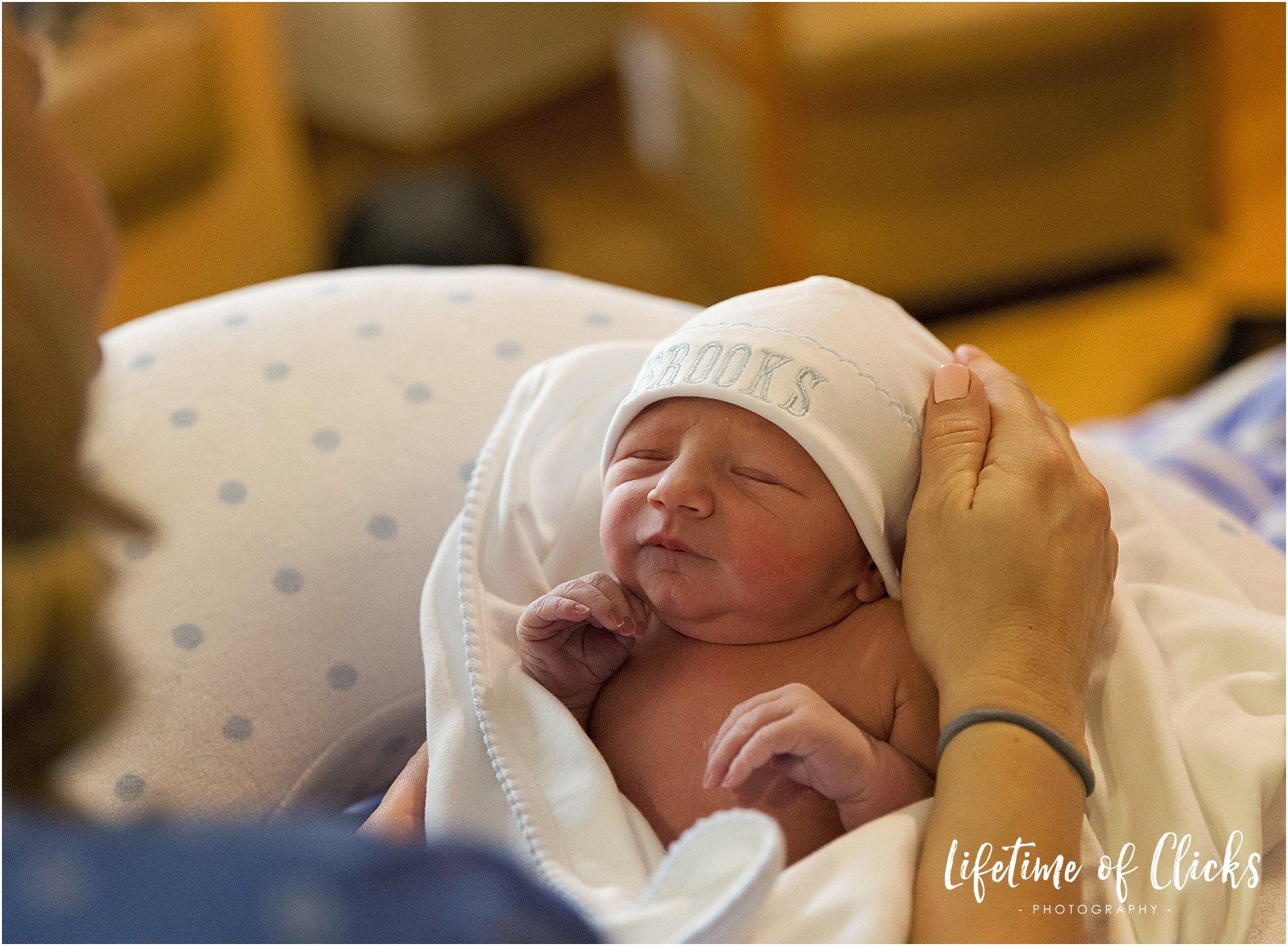 Newborn boy wearing embroidered hat