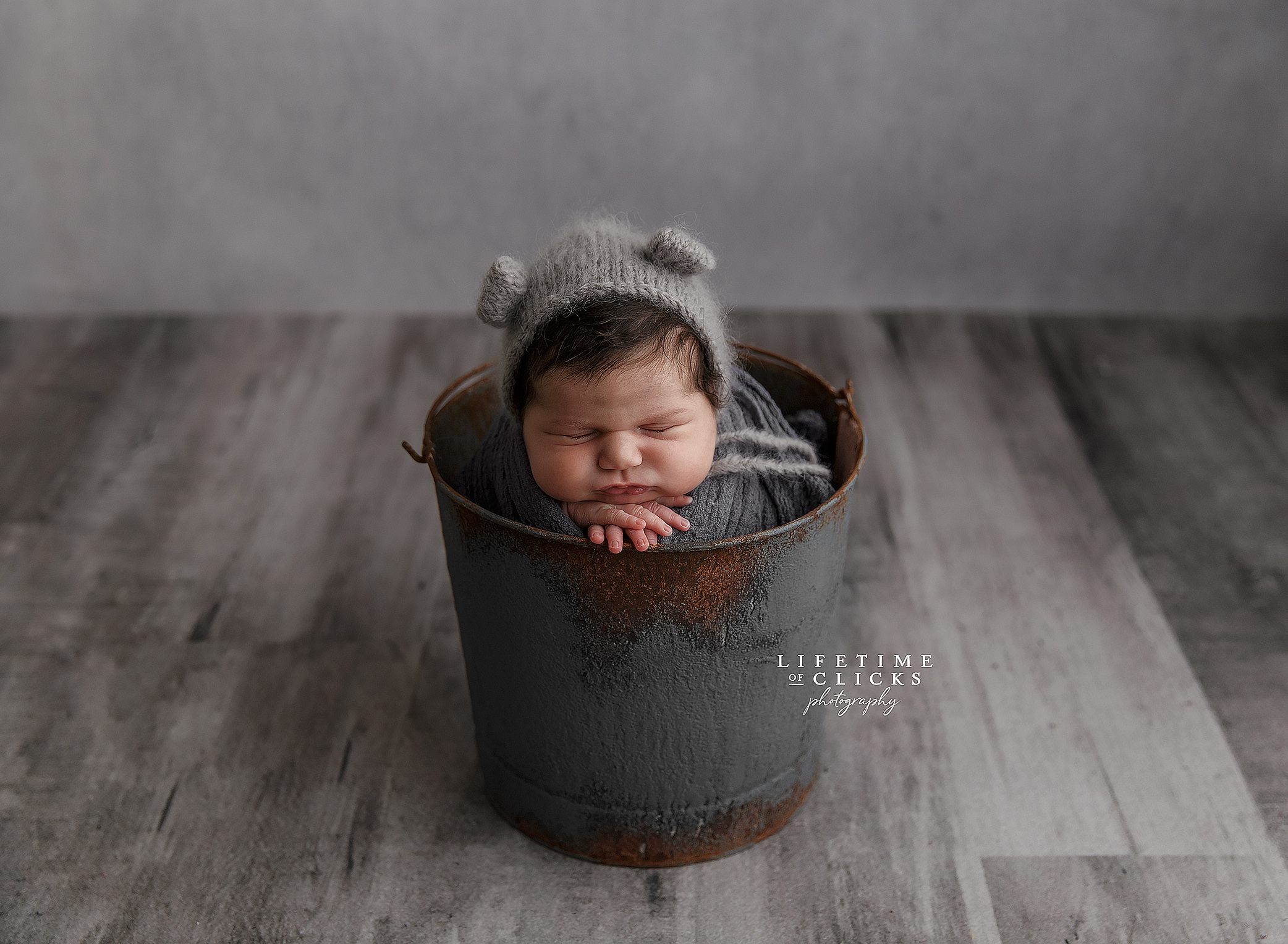 newborn girl in gray bucket with gray bear hat