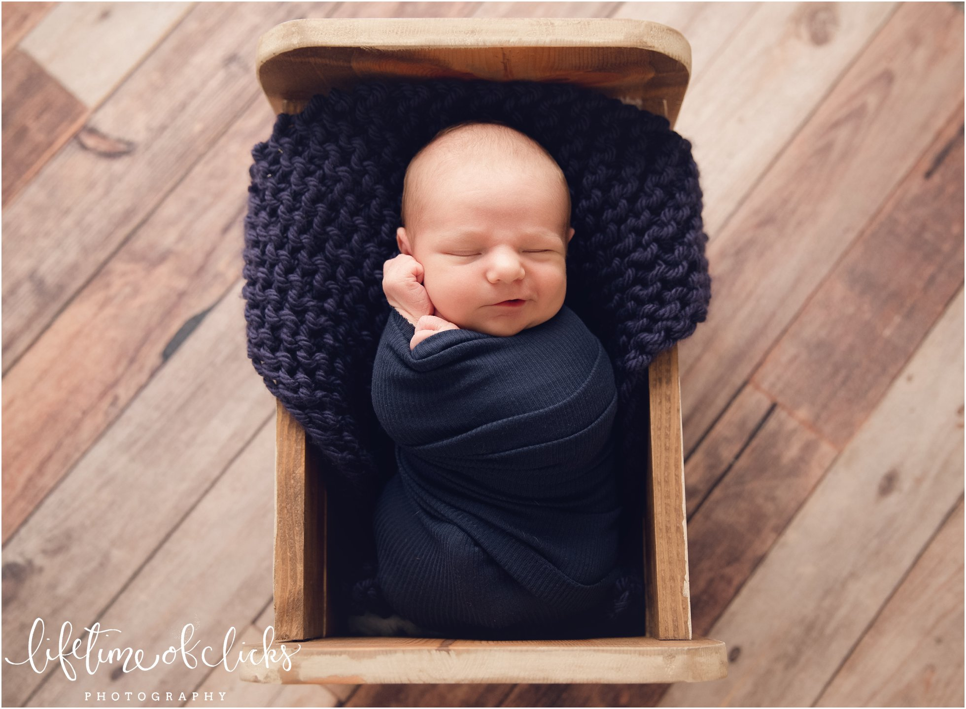 Newborn with smirk on his face by Newborn Photographer Houston TX