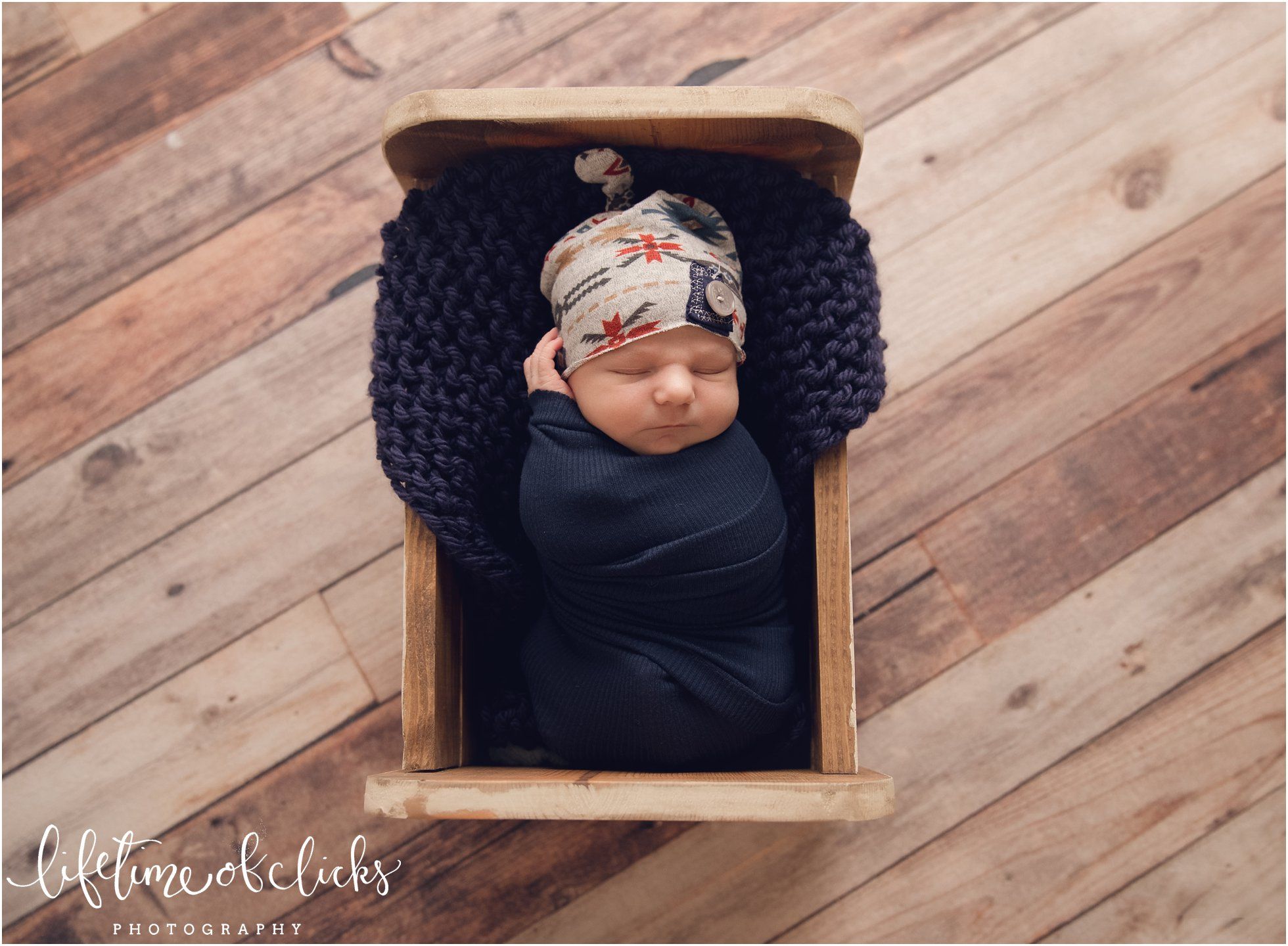 Newborn in crate | Photo by Lifetime of Clicks Photography