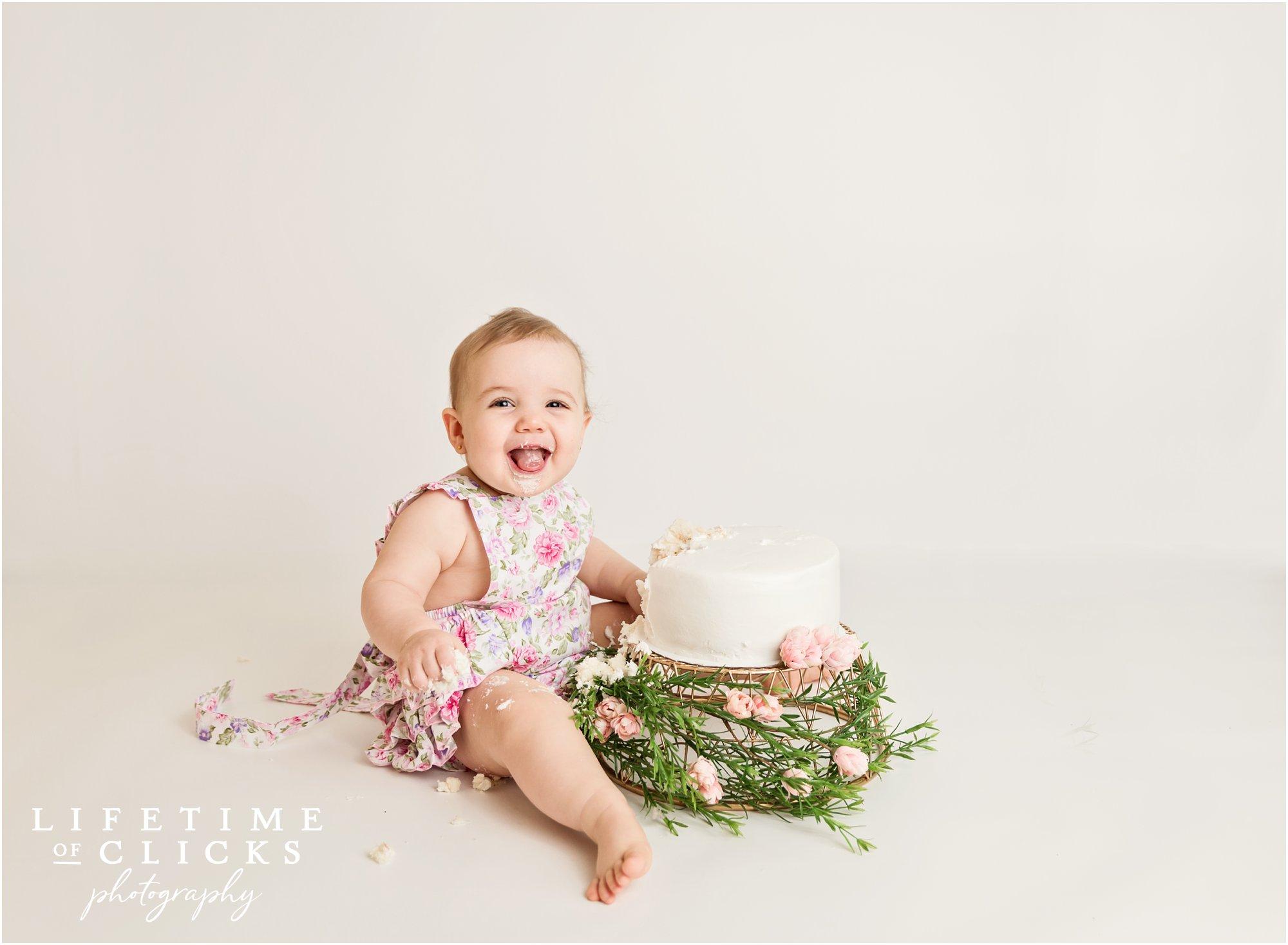 baby girl smiling during cake smash session