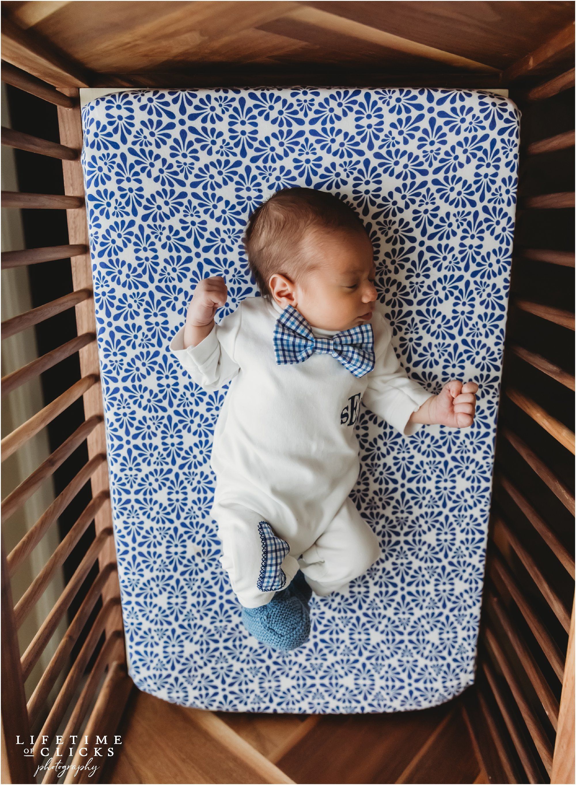 Newborn boy wearing white onesie and blue plaid bow tie sleeping in a bassinet