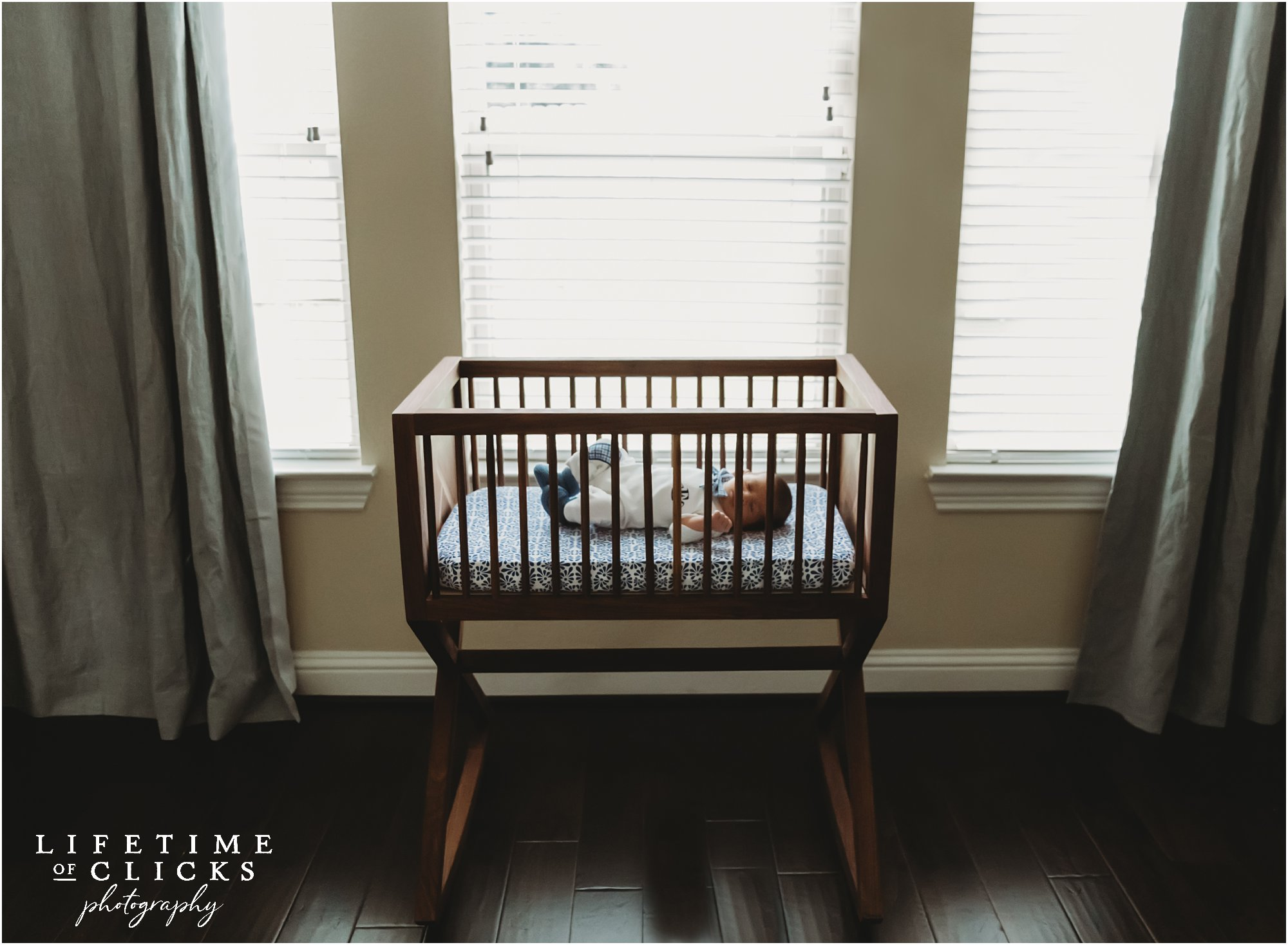 Newborn boy in a dark wood bassinet