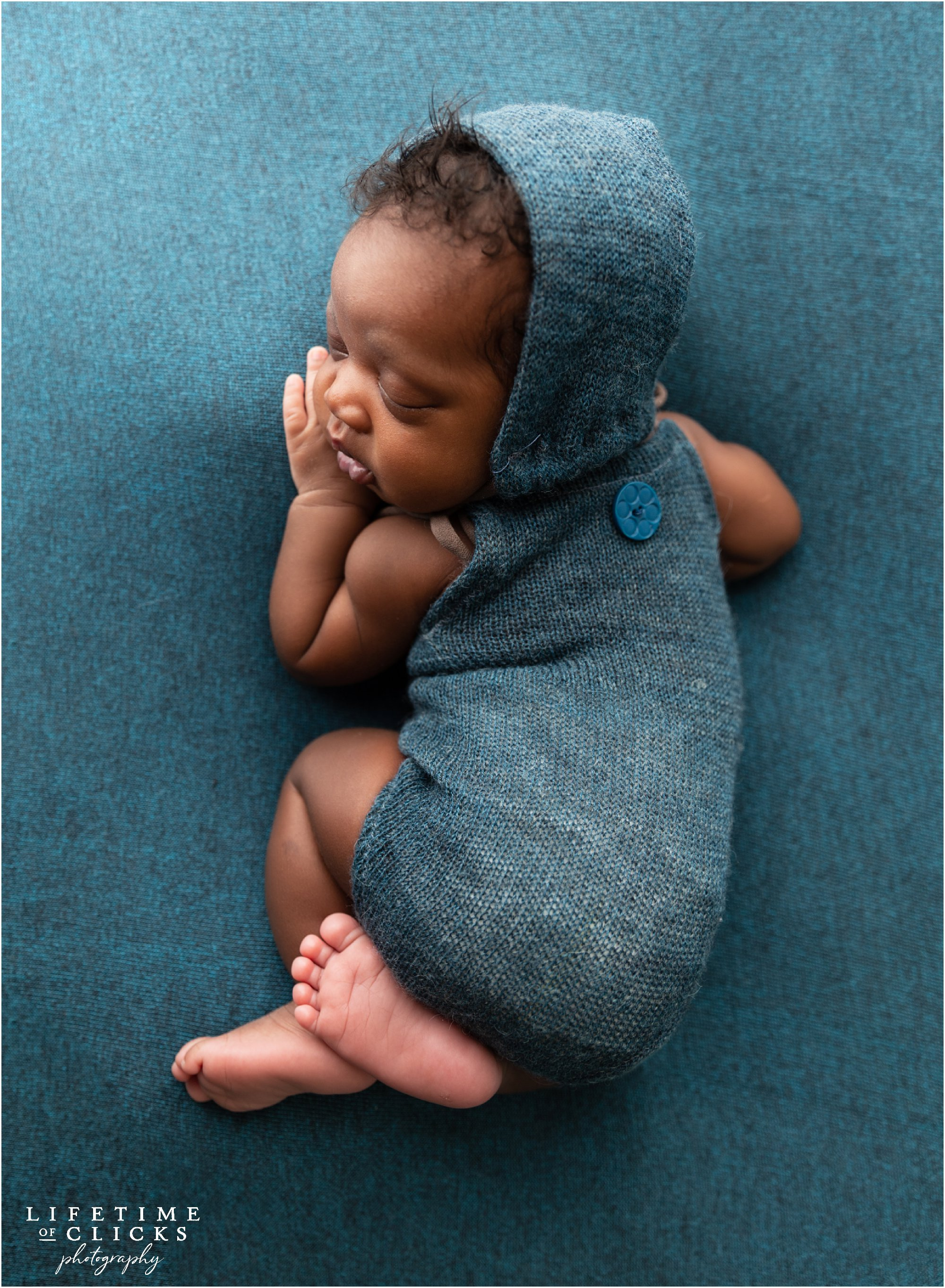 Newborn boy sleeping on a blue blanket and blue romper