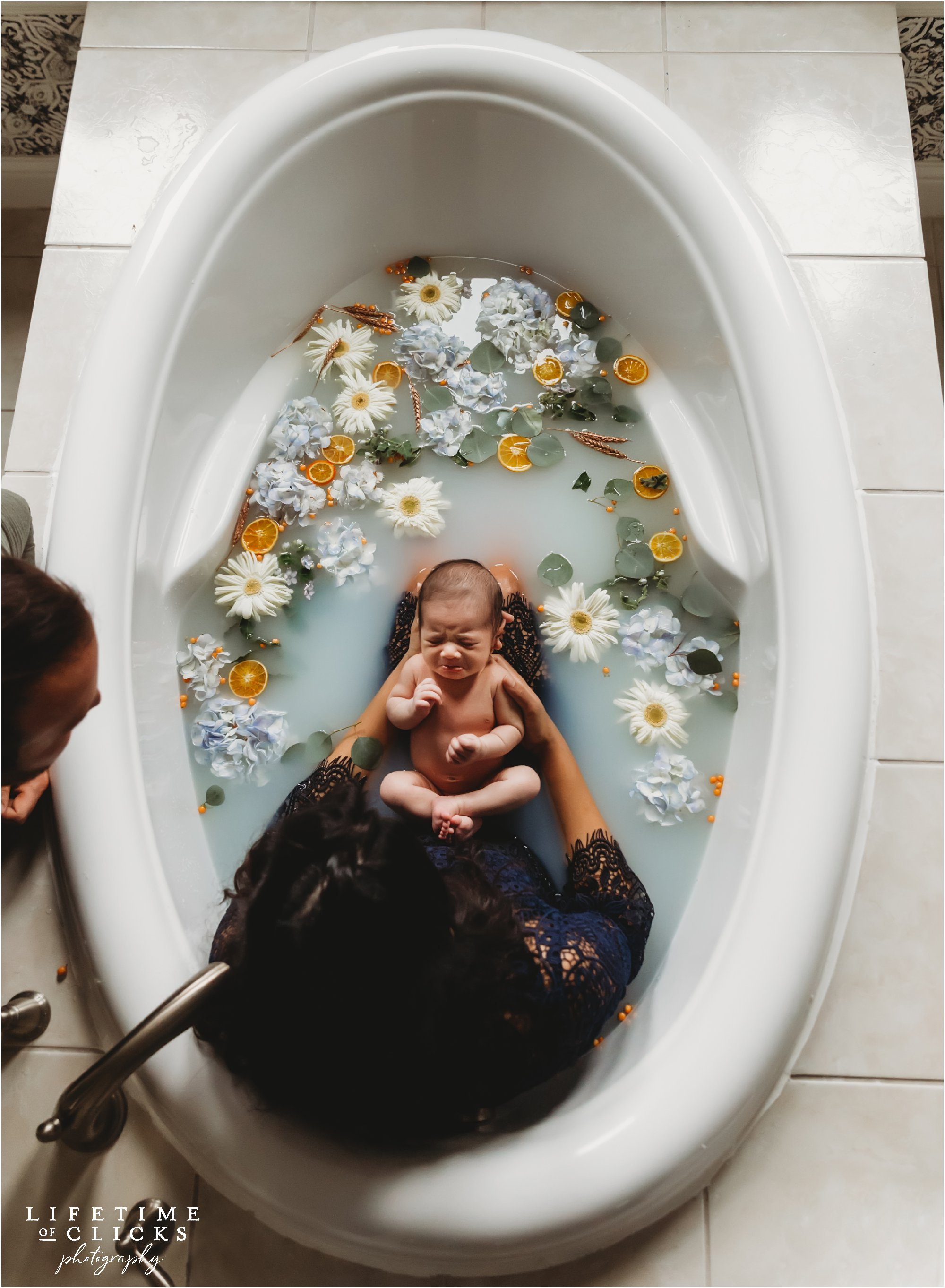 Newborn boy in milk bath with mother | Photos by Lifetime of Clicks Photography