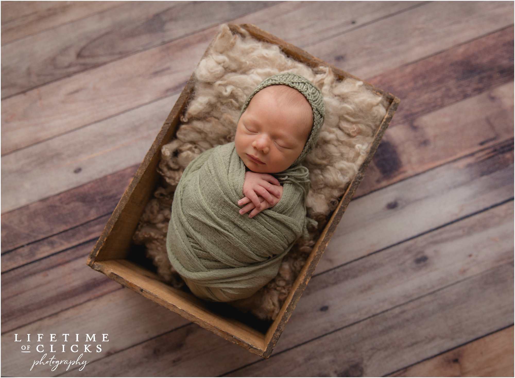 newborn boy asleep in a crate