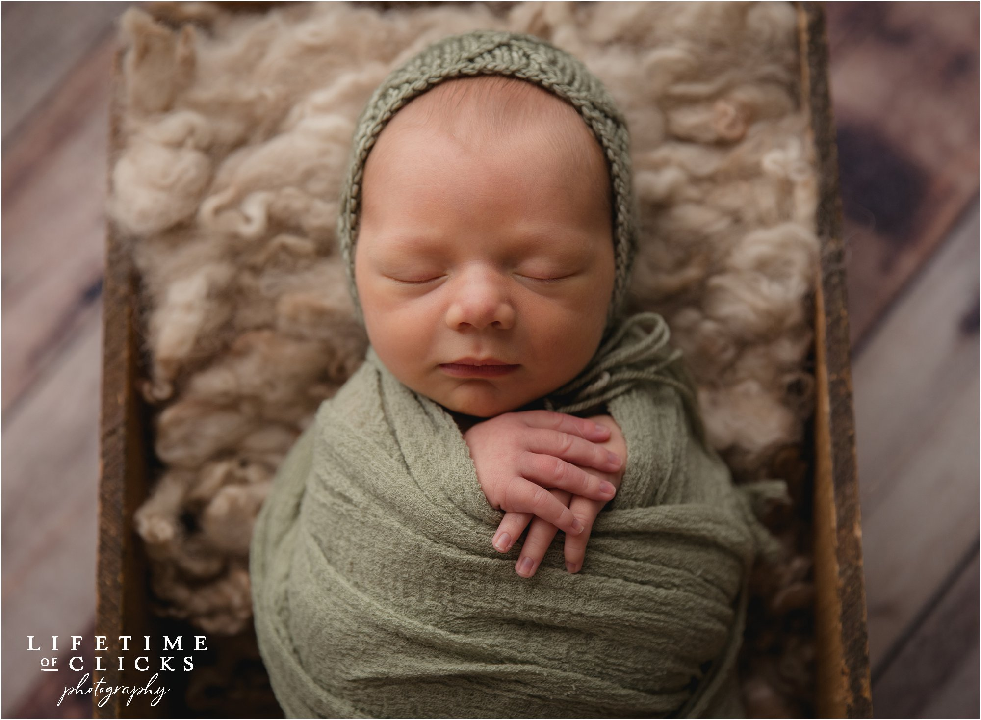 newborn boy in a green wrap and hat