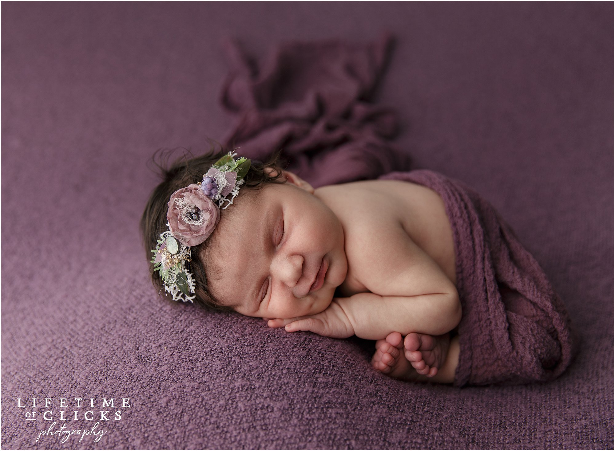 newborn girl in dark purple blankets