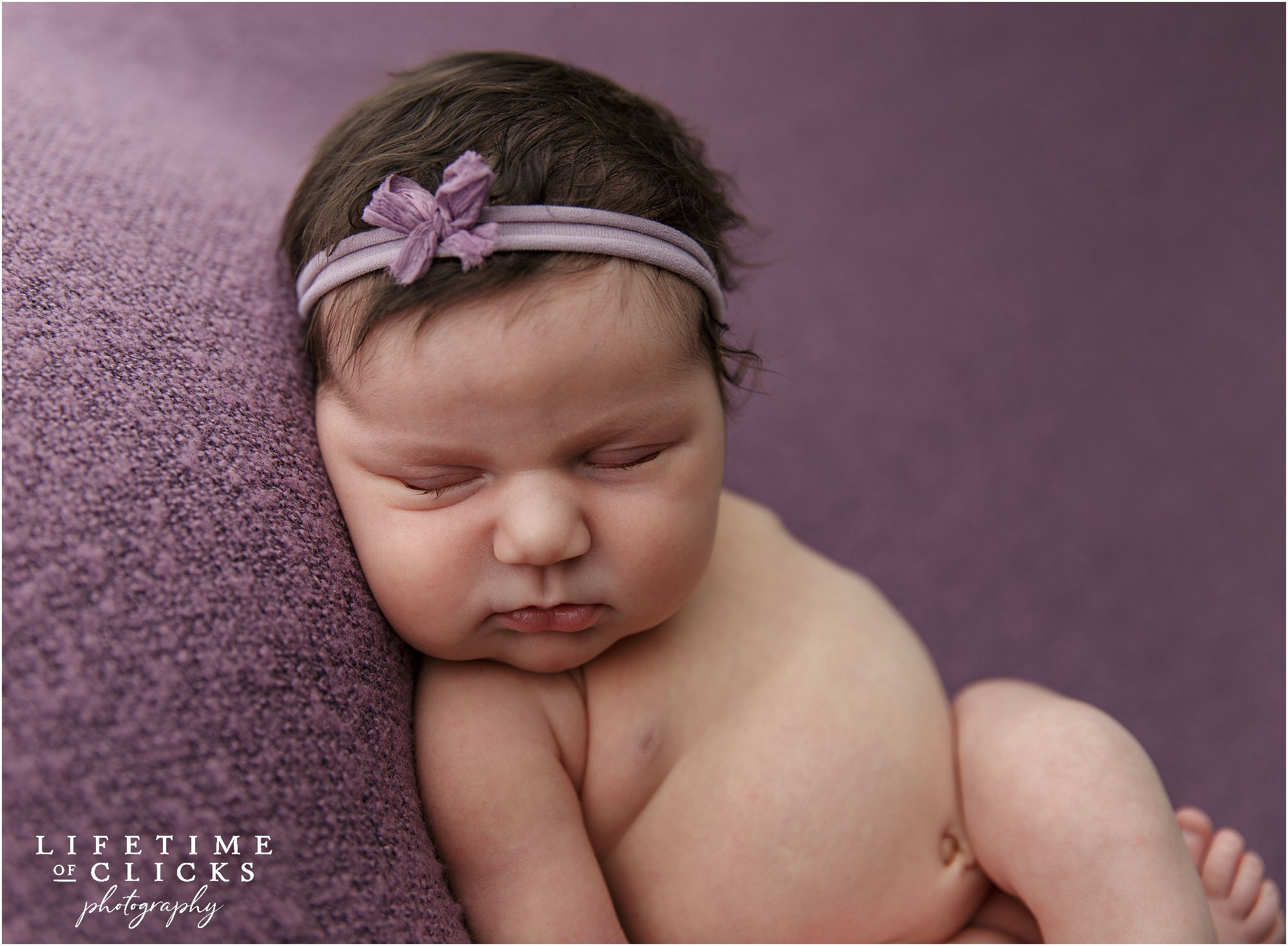 newborn girl with purple bow