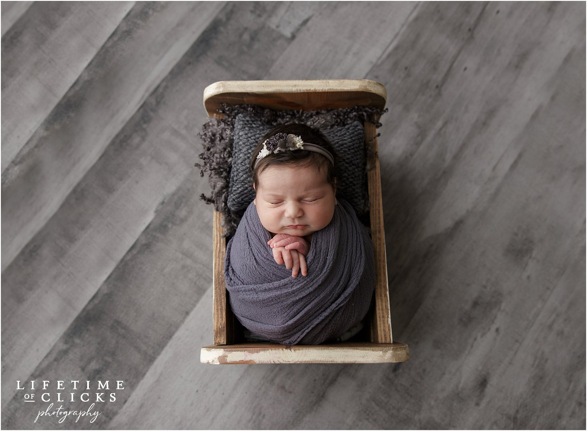newborn girl snuggled in wooden bed