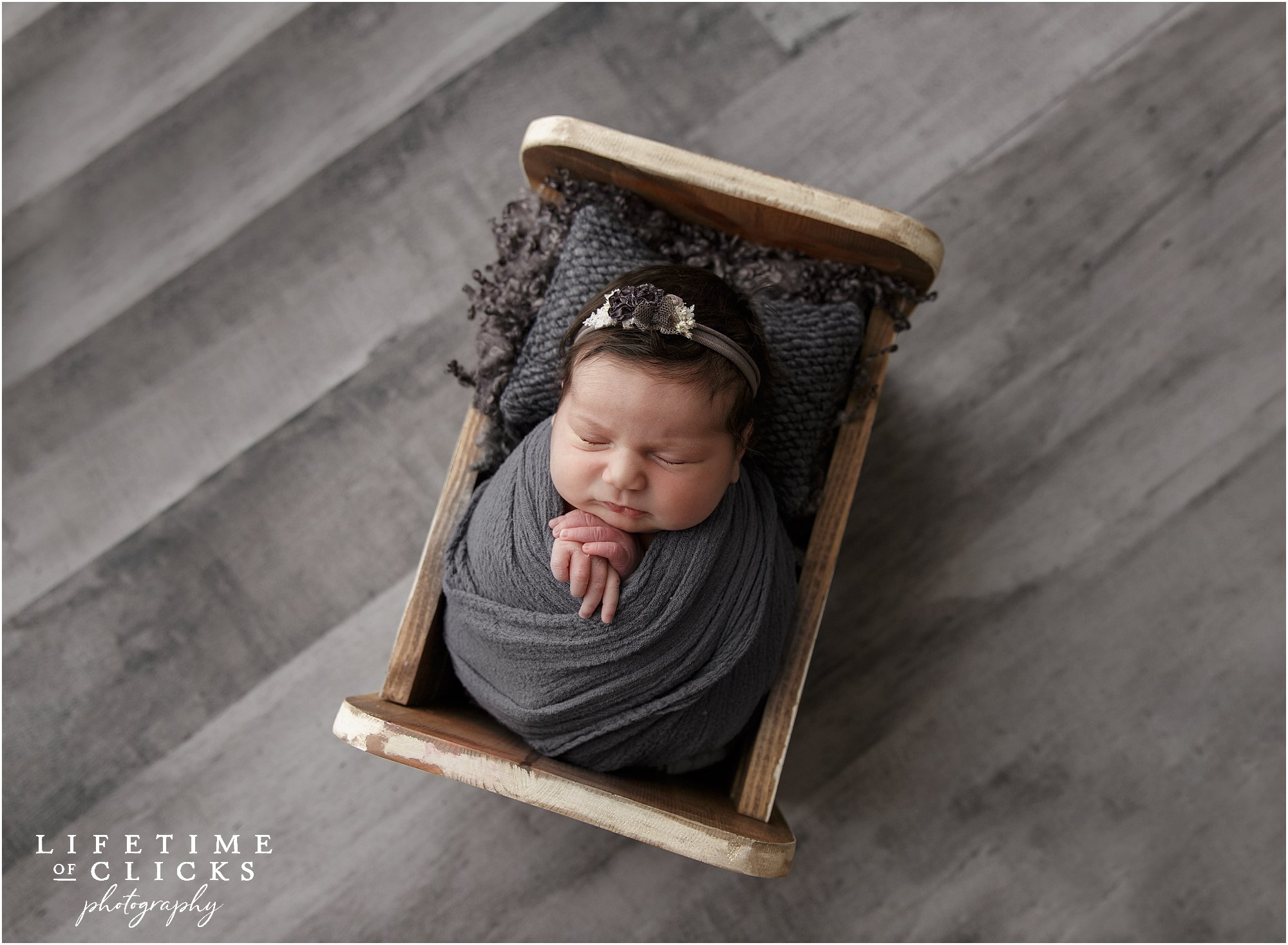 newborn girl in wooden bed