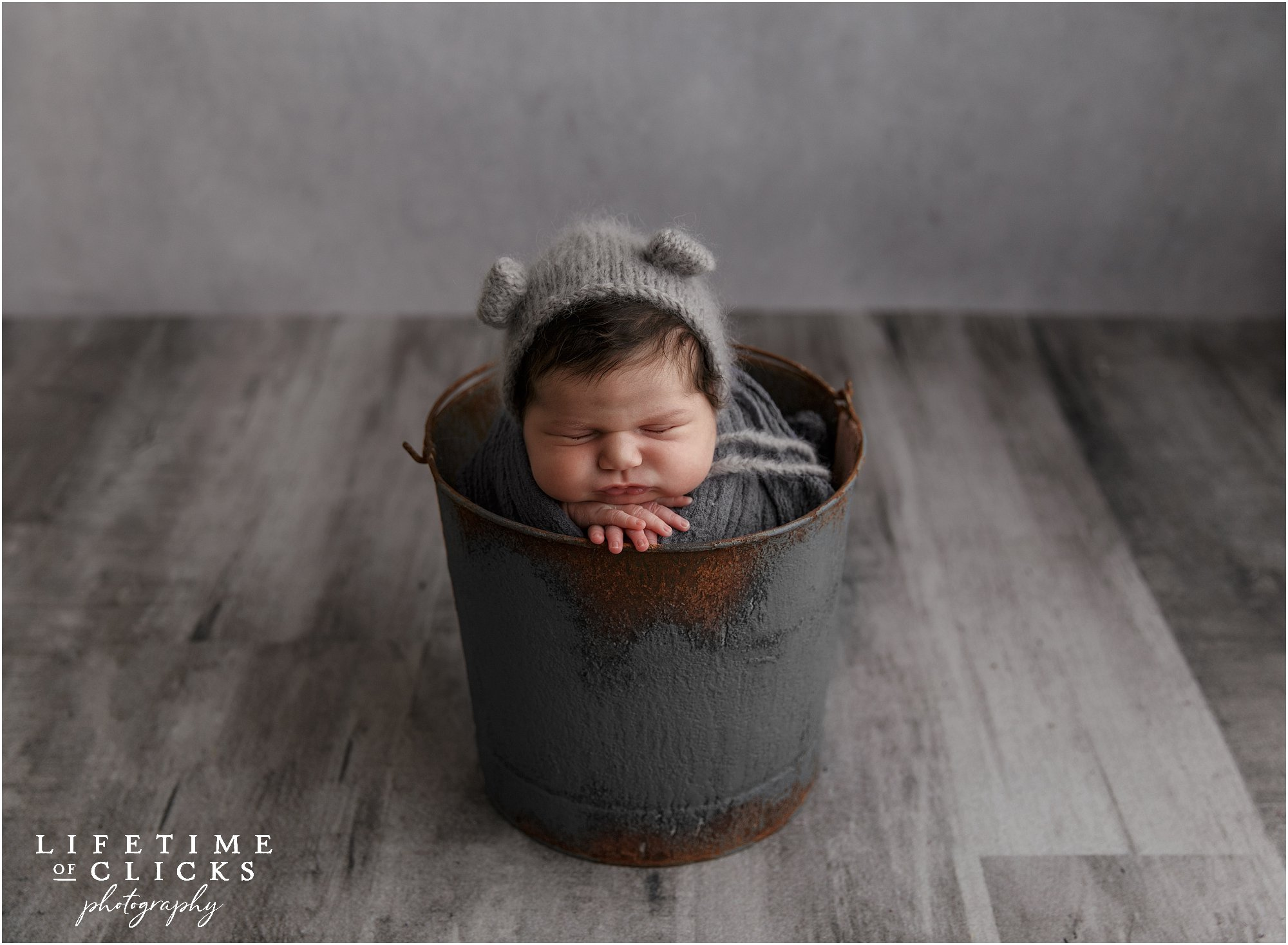 newborn boy in a gray bucket
