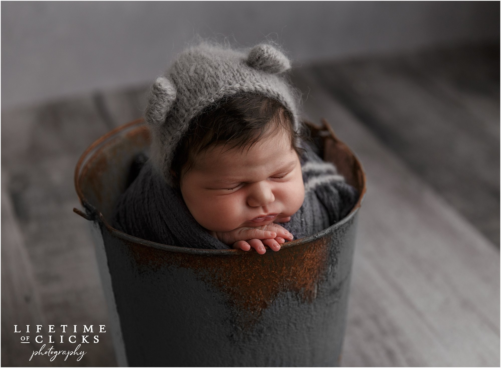 newborn girl in bucket pose