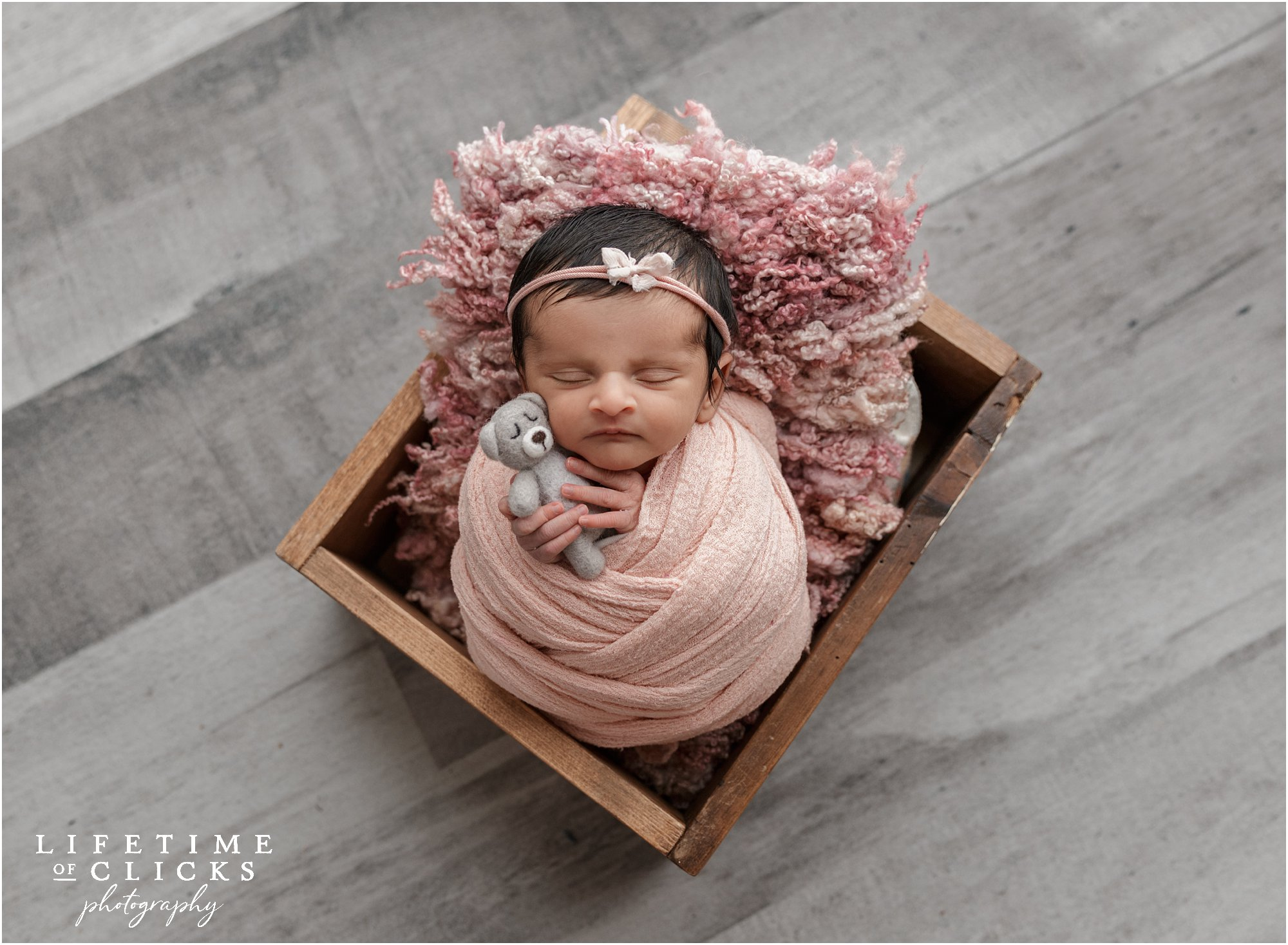 newborn girl in wooden crate and lovey
