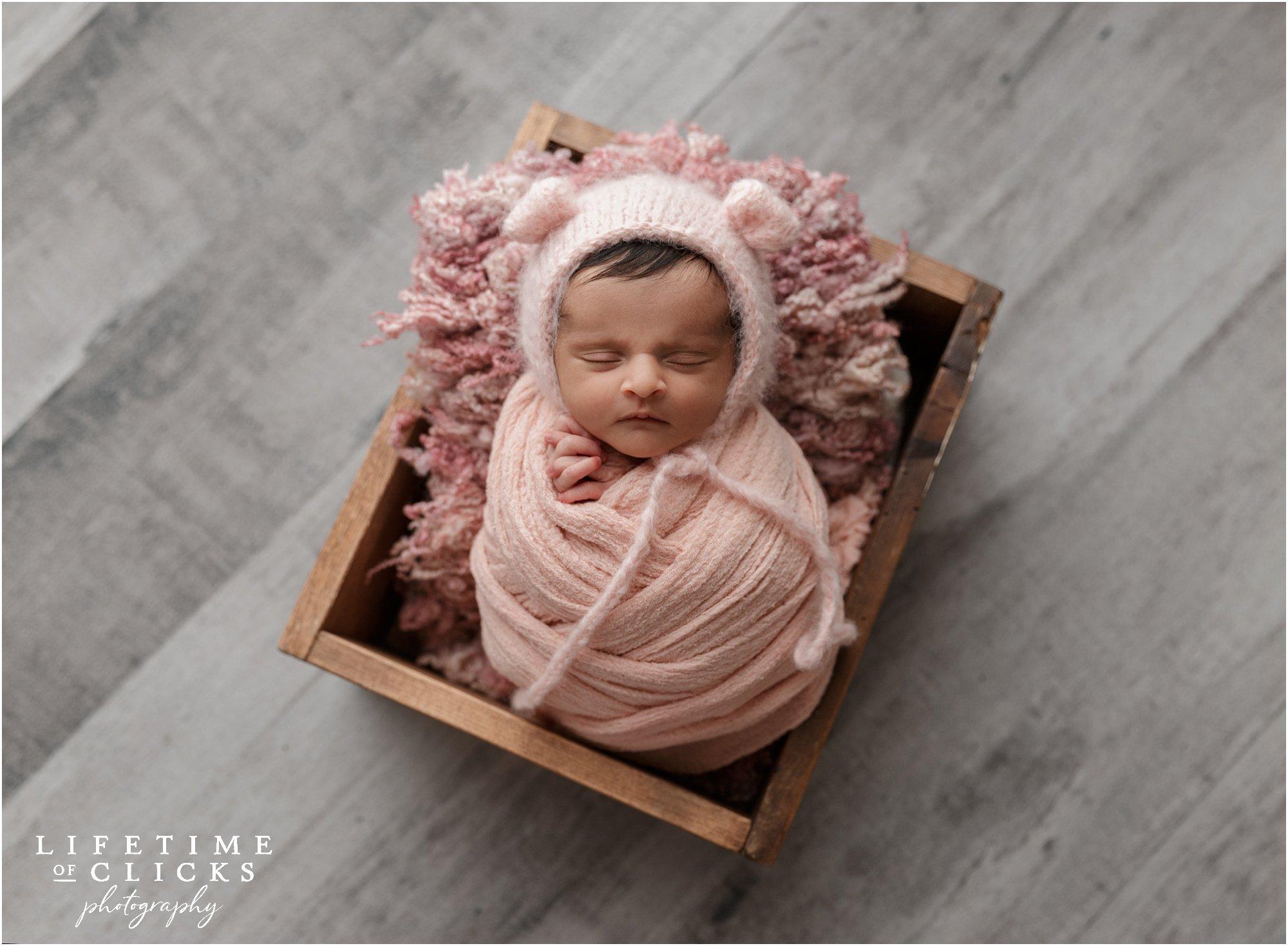 newborn girl in pink wraps