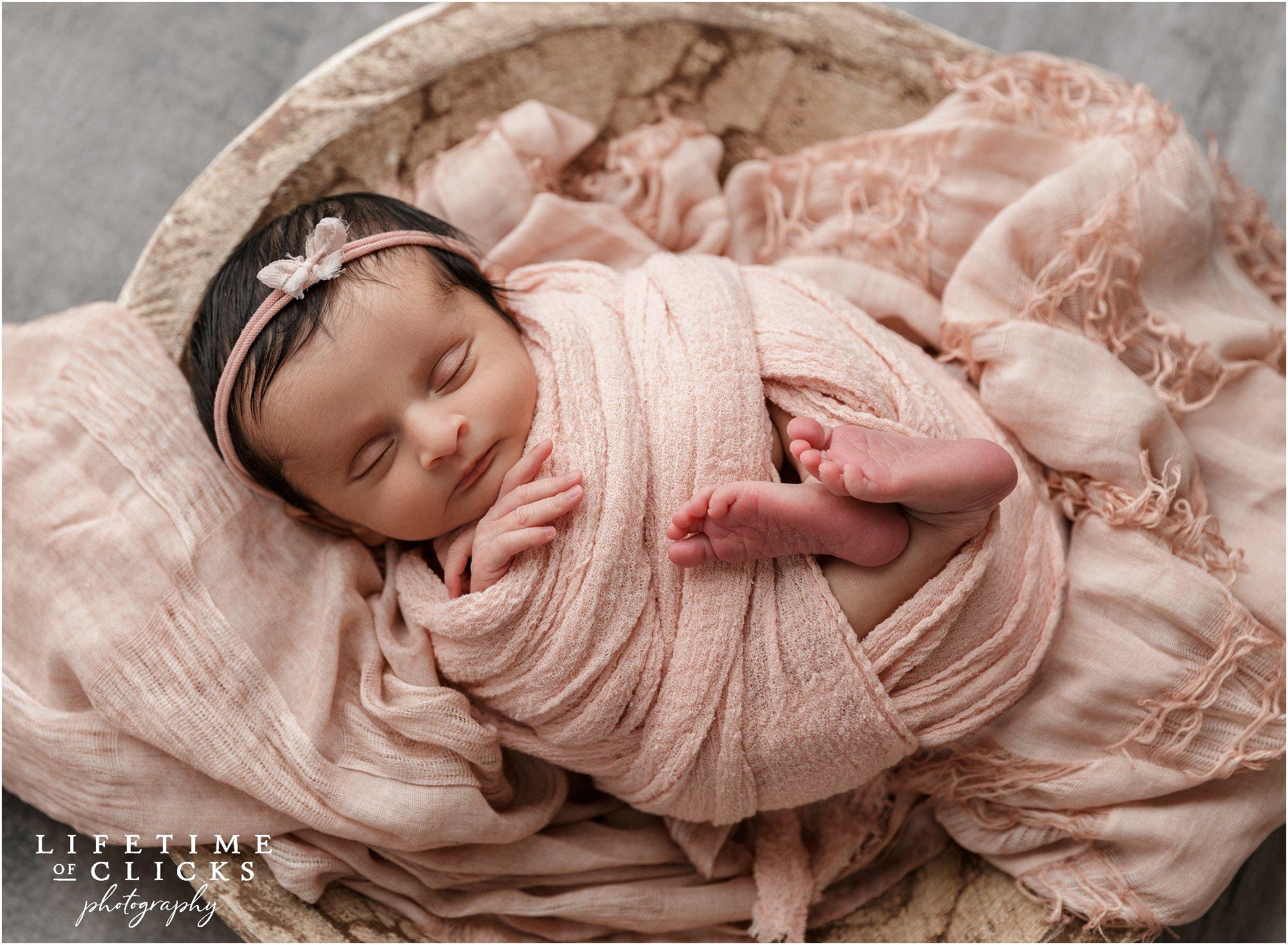 newborn girl in beige bowl