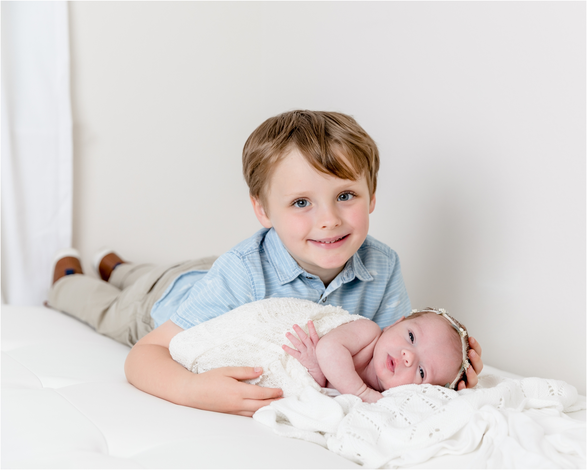 Big brother laying next to baby during newborn session in Katy TX studio. Photo by Lifetime of Clicks Photography.