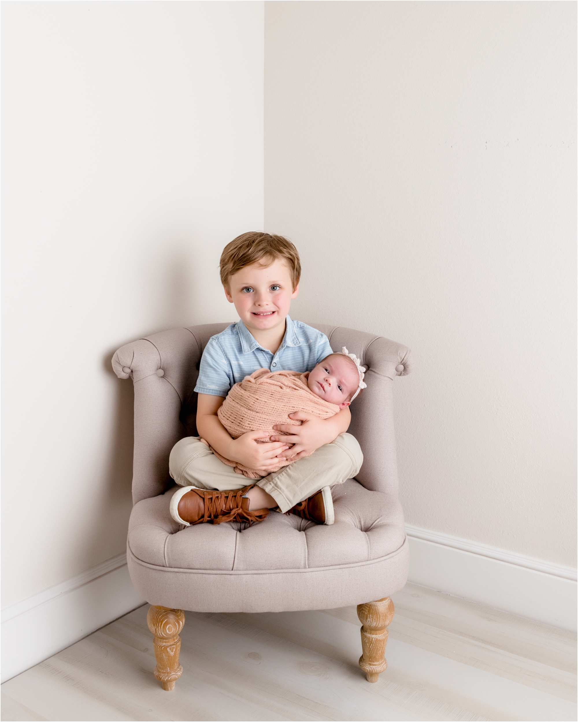 Big brother holding sister while smiling at the camera. Photo by Lifetime of Clicks Photography.