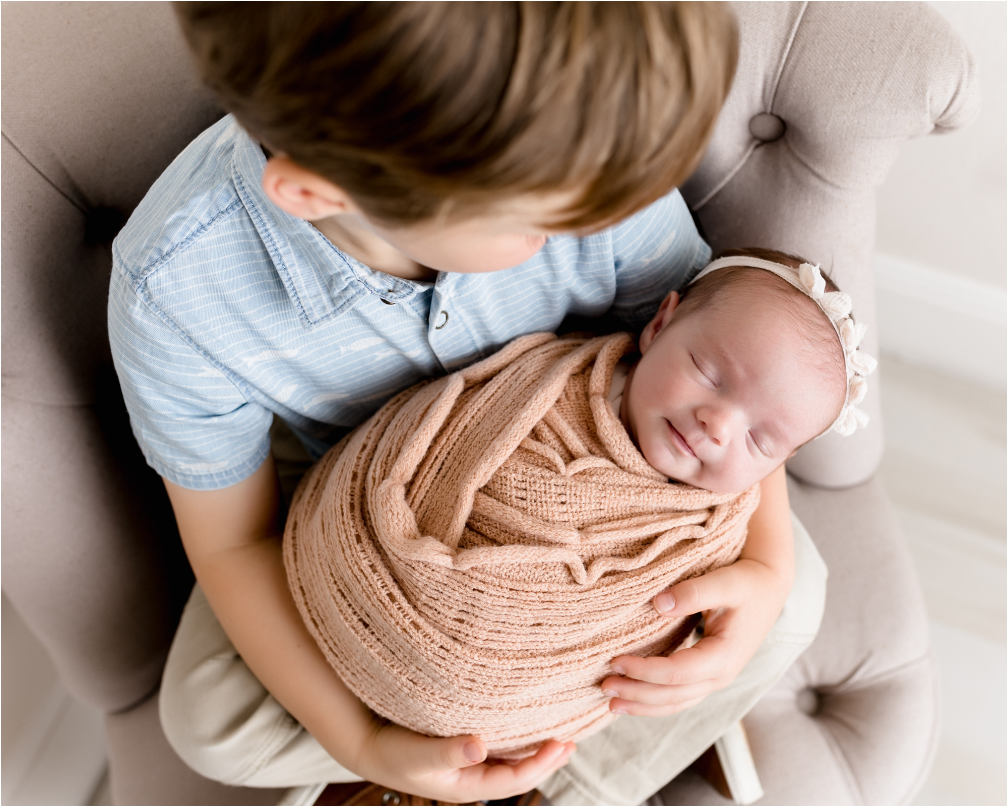 Image of baby sister being held by brother while baby is swaddled. Photo by Katy TX newborn photographer, Lifetime of Clicks Photography.
