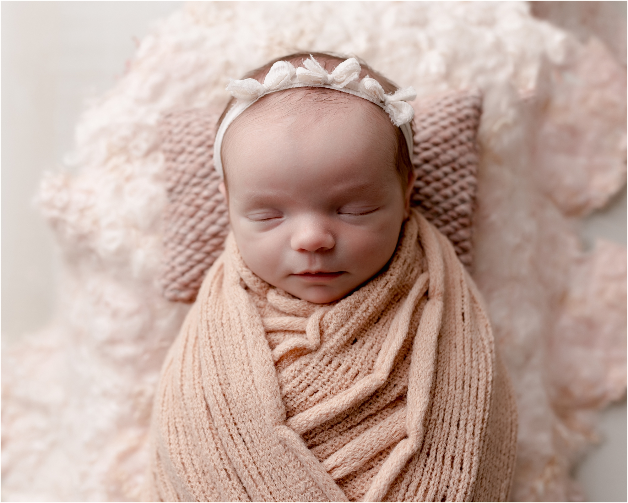Baby girl sleeping in textured swaddles during studio newborn session. Photo by Lifetime of Clicks Photography.