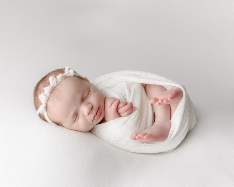 Baby girl in white swaddle during posed newborn session by Katy TX newborn photographer, Lifetime of Clicks Photography.