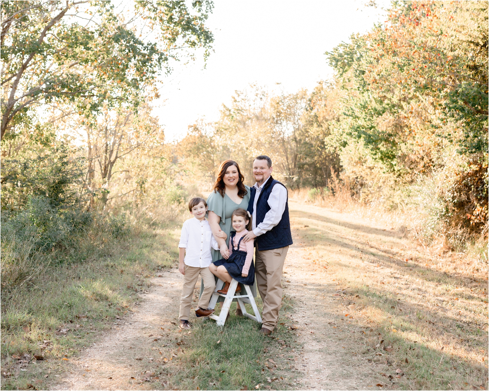 Sweet family portrait with parents and two kids smiling at camera. Photo by family photographer in Katy TX, Lifetime of Clicks Photography.