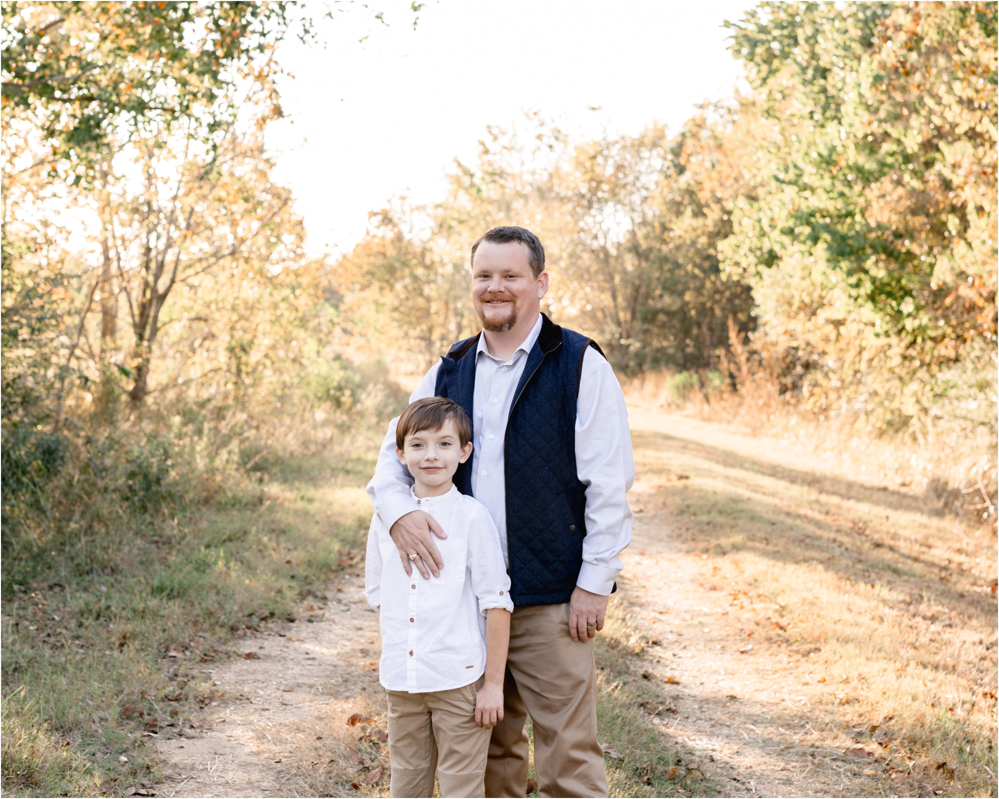 Dad hugging son in park during sunset family session with Katy TX family photographer, Lifetime of Clicks Photography.