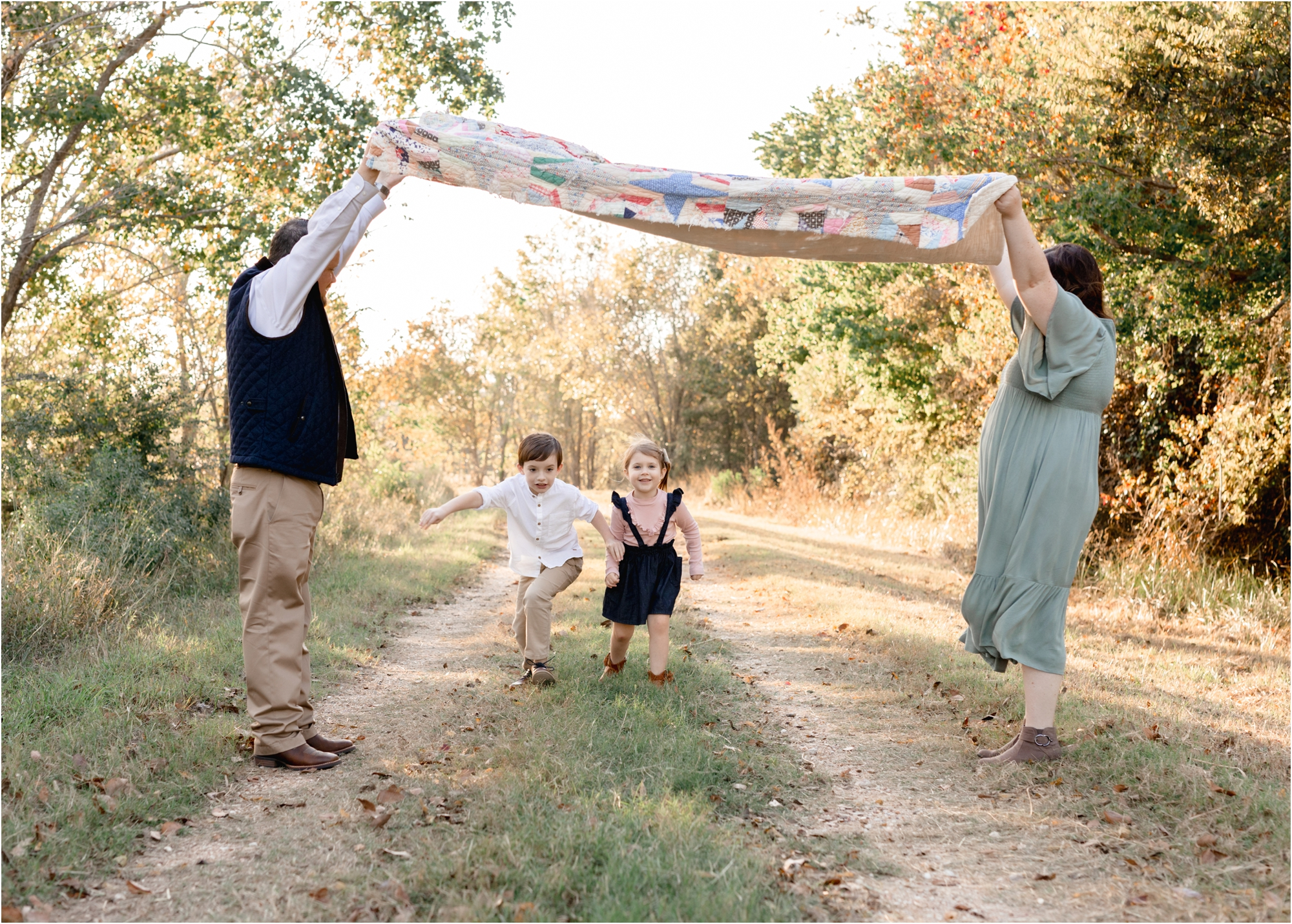 Parents playing with kids running under blanket during family session in Katy, TX park. Photo by Lifetime of Clicks Photography.