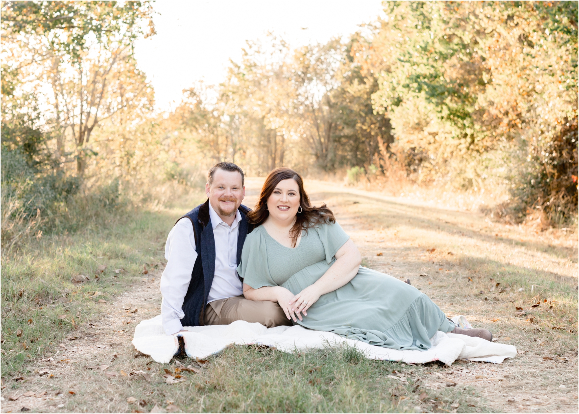 Mom and Dad sitting together on blanket during family session in Katy, TX. Photo by Lifetime of Clicks Photography.