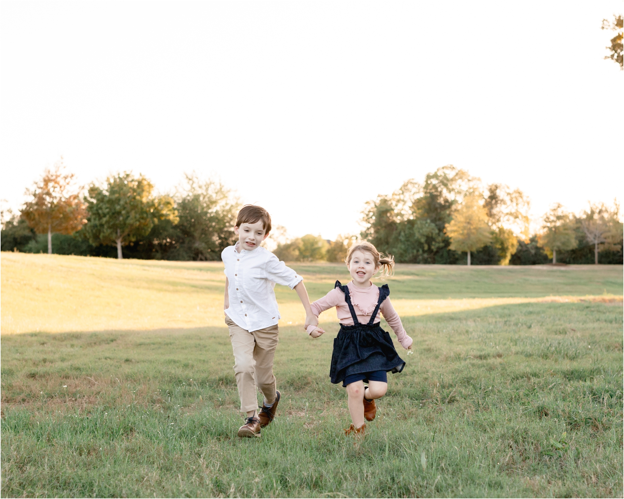 Kids running through sunlit field during family session. Photo by Lifetime of Clicks Photography.