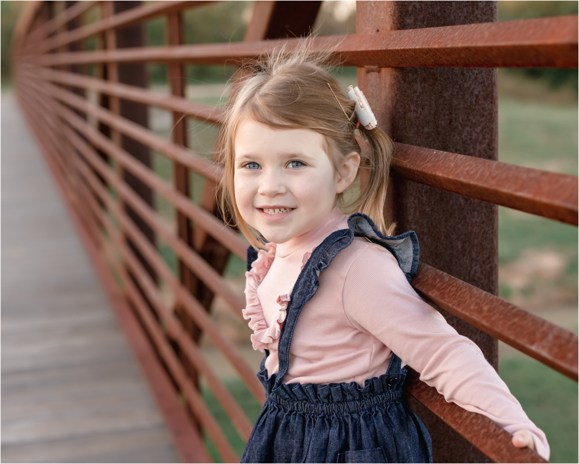 Closeup of little girl leaning on bridge and smiling at camera. Photo by Lifetime of Clicks Photography.