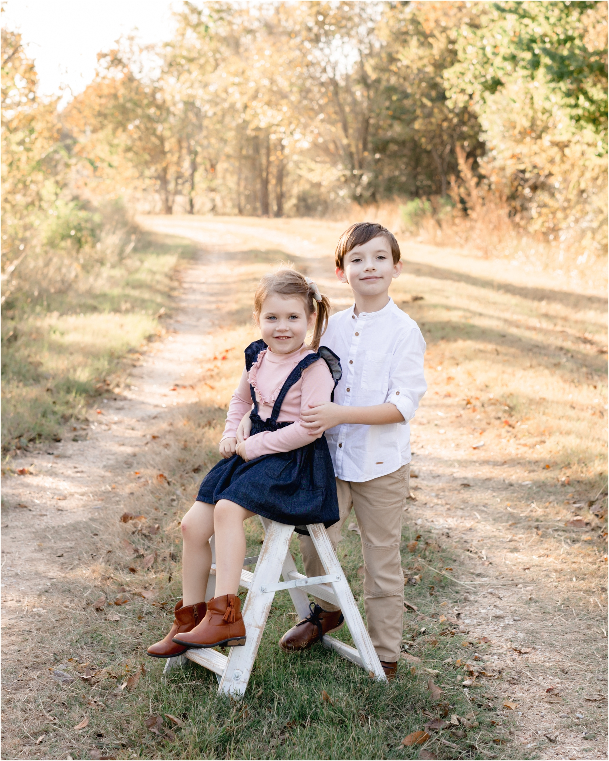 Brother and sister smiling at the camera during a family session by Lifetime of Clicks Photography.