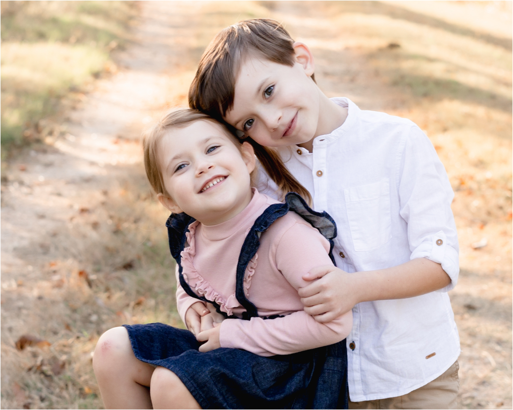 Closeup of brother and sister hugging during family photoshoot. Photo by family photographer in Katy TX, Lifetime of Clicks Photography.