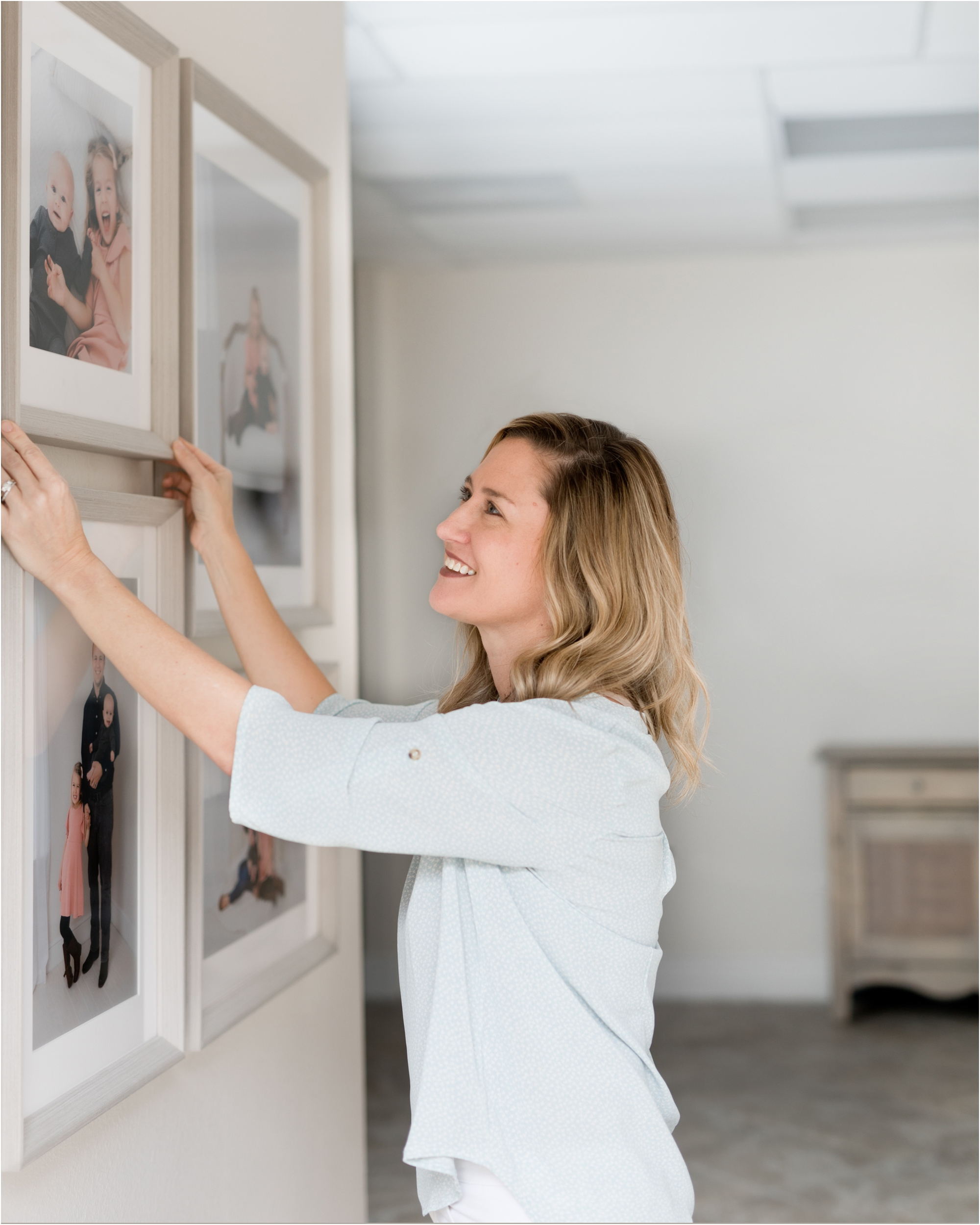 Image of Kelly from Lifetime of Clicks Photography installing framing.