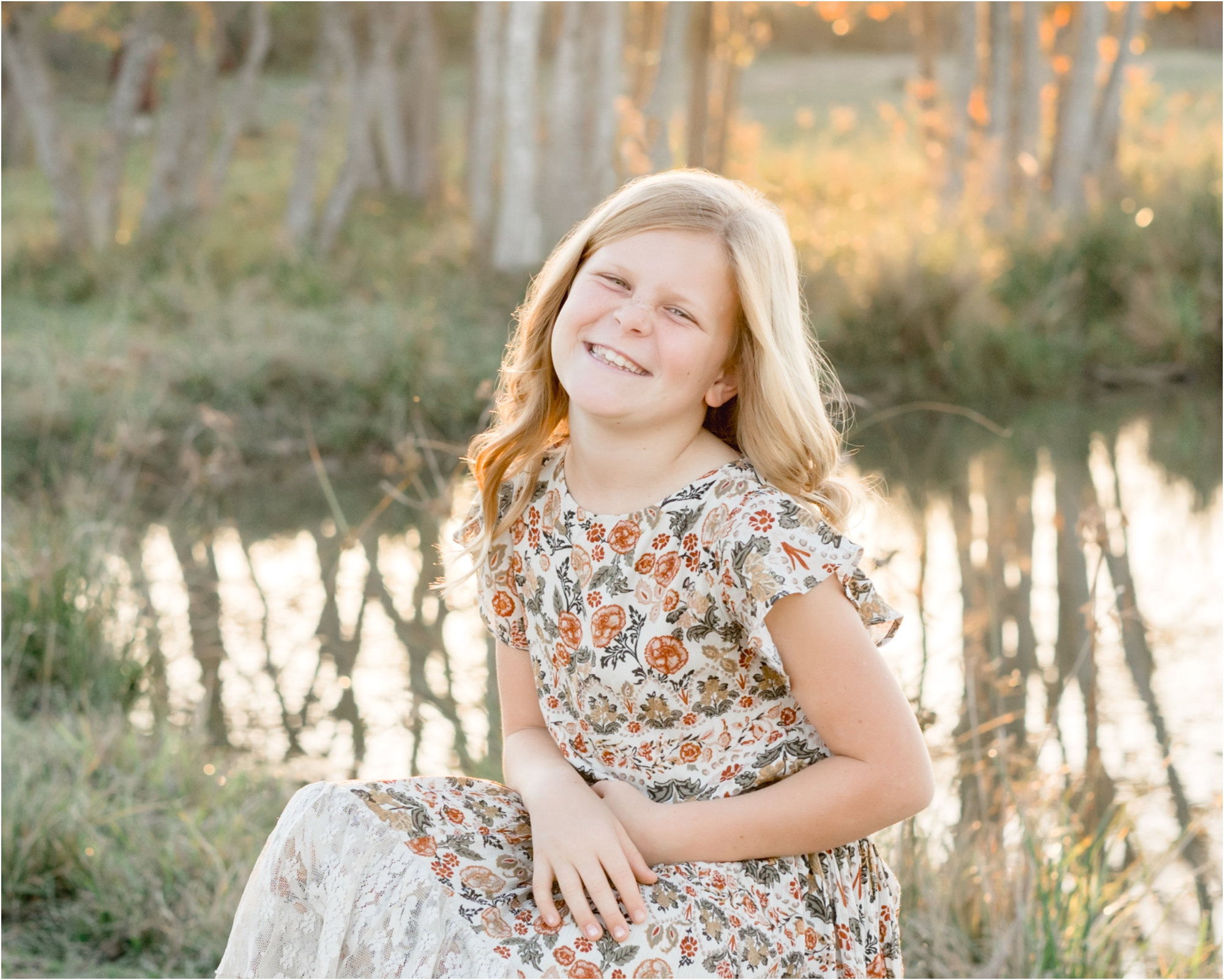 Smiling oldest daughter during family session in backyard with sunlight on pond. Photo by Lifetime of Clicks Photography.