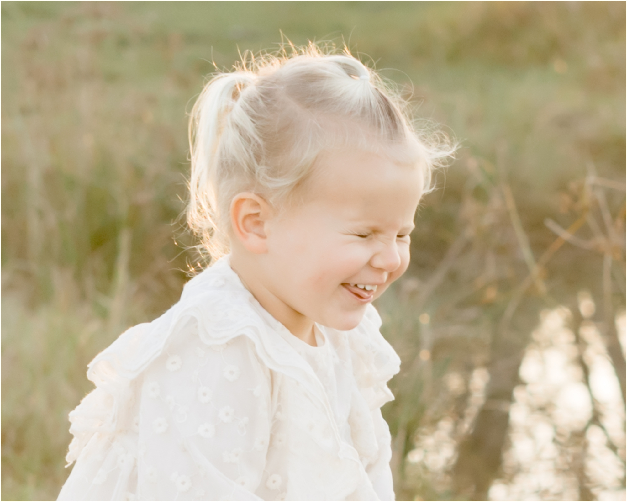 Laughing girl during family session. Photo by Lifetime of Clicks Photography.