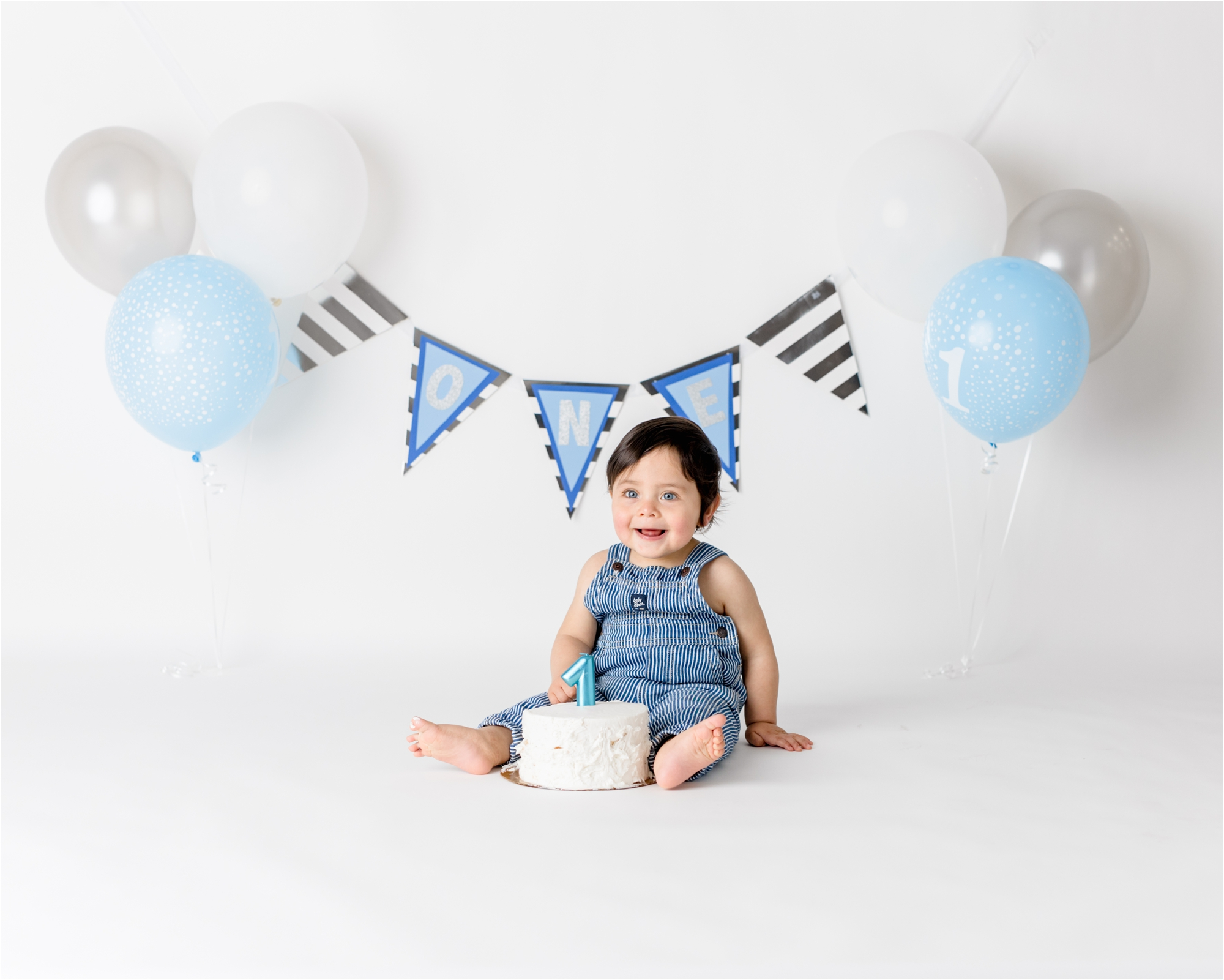 Baby boy on white backdrop with blue, silver and white themed cake smash. Photo by Lifetime of Clicks Photography.