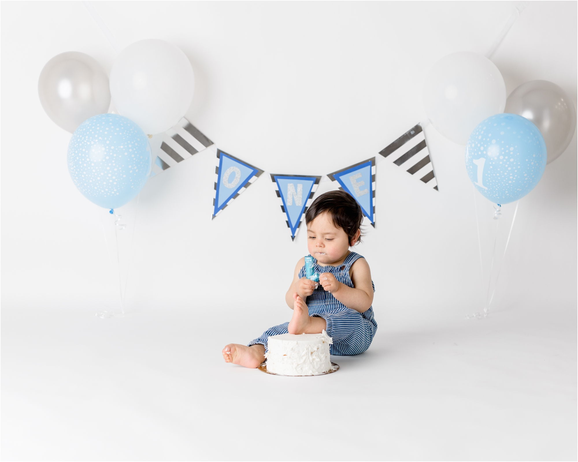Baby boy starting to dig into his cake during first birthday cake smash session at Houston TX studio. Photo by Lifetime of Clicks Photography.