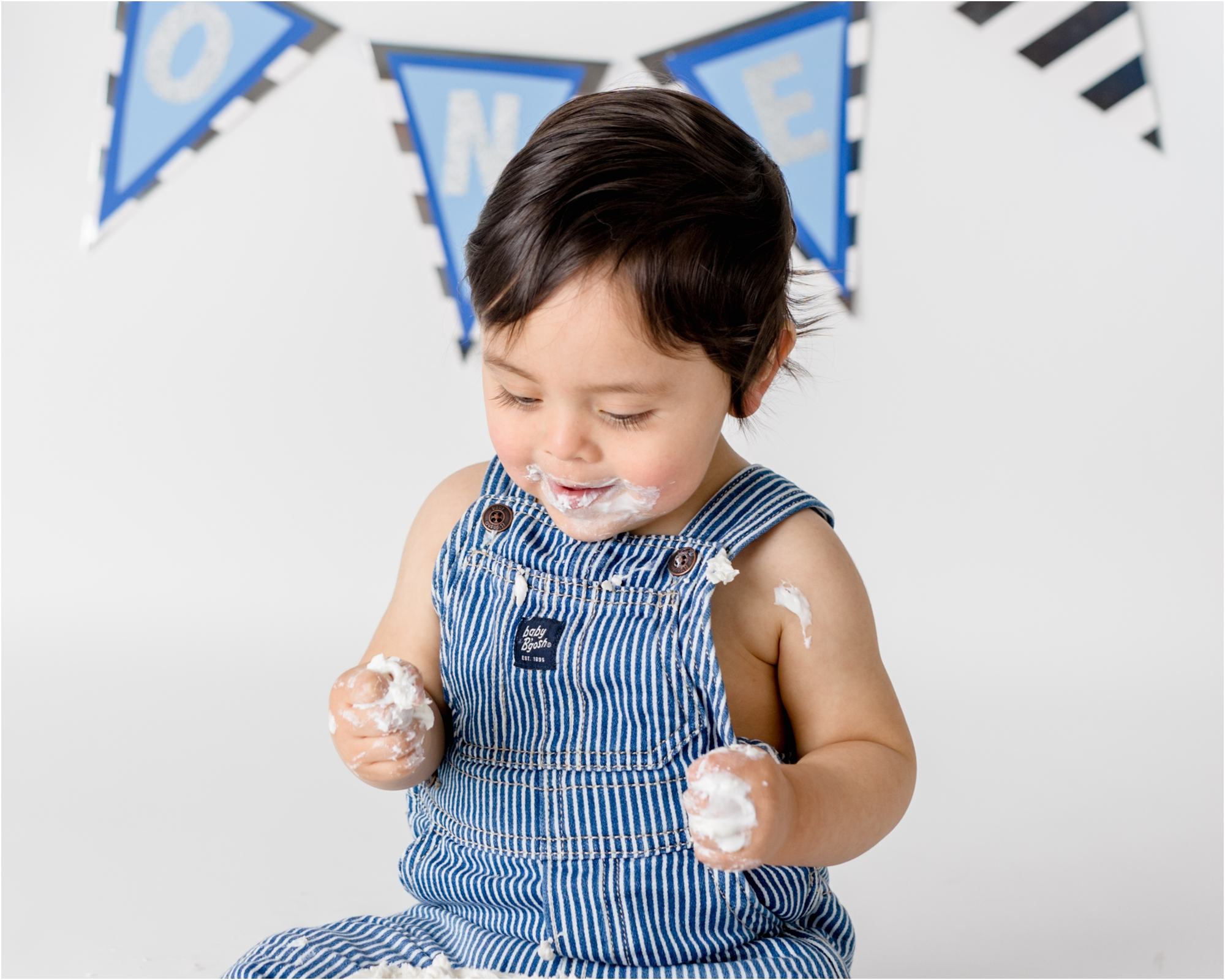 First birthday milestone session for little boy with white and blue cake smash. Photo by Lifetime of Clicks Photography.