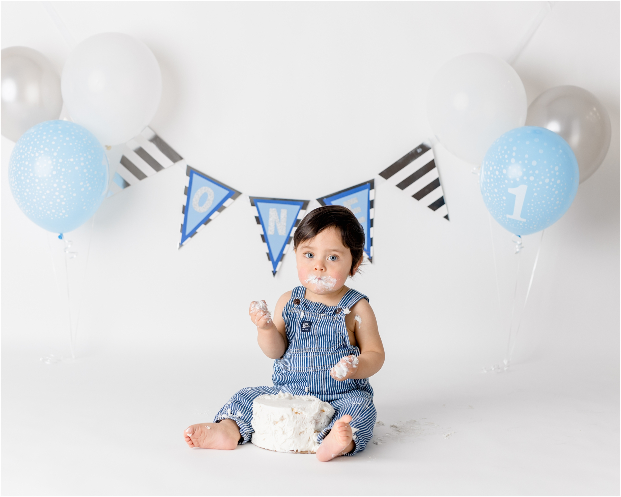 Boy's cake smash session with white, blue and silver theme and simple, classic decor. Photo by Houston family photographer, Lifetime of Clicks Photography.