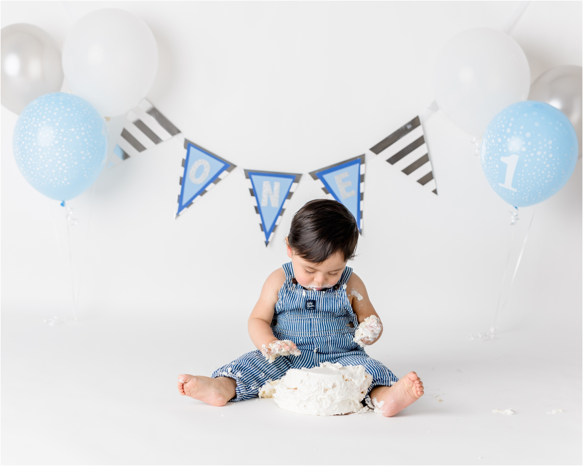 Little boy playing with frosting from cake. Photo by Lifetime of Clicks Photography.
