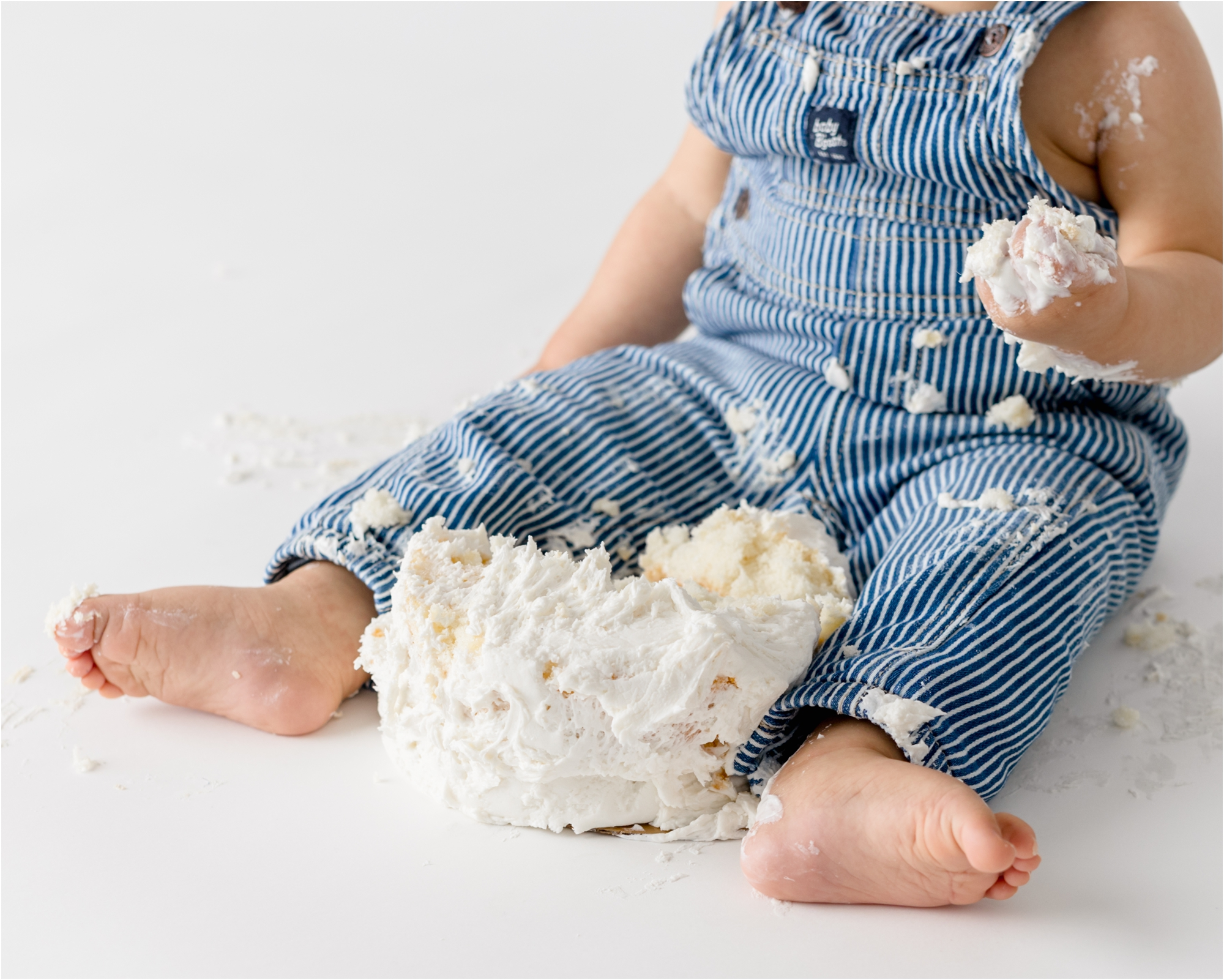 Baby boy's feet and hands covered in frosting during cake smash session in Houston. Photo by Lifetime of Clicks Photography.