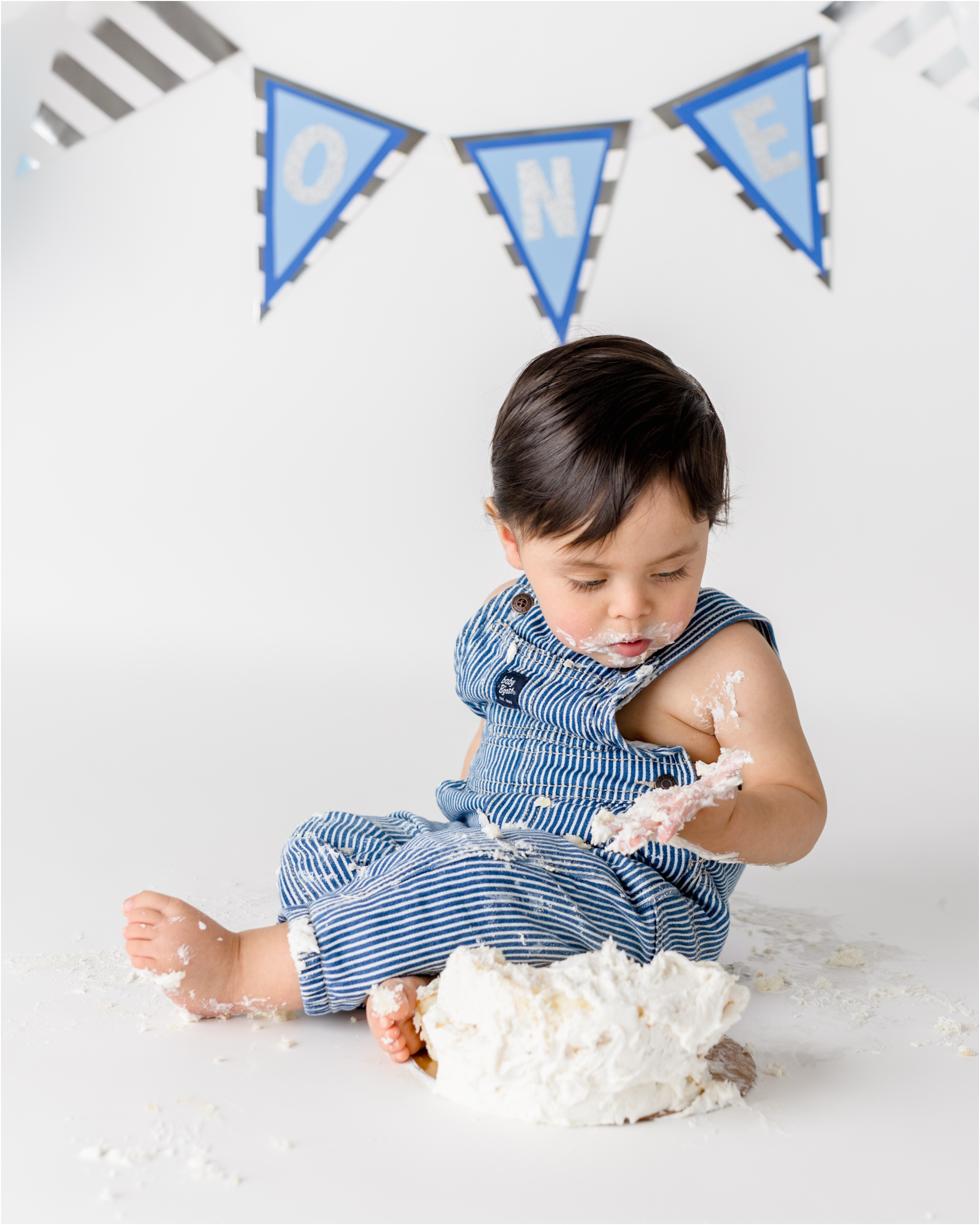 Baby boy in blue striped overalls looking at frosting on hands. Photo by Lifetime of Clicks Photography.