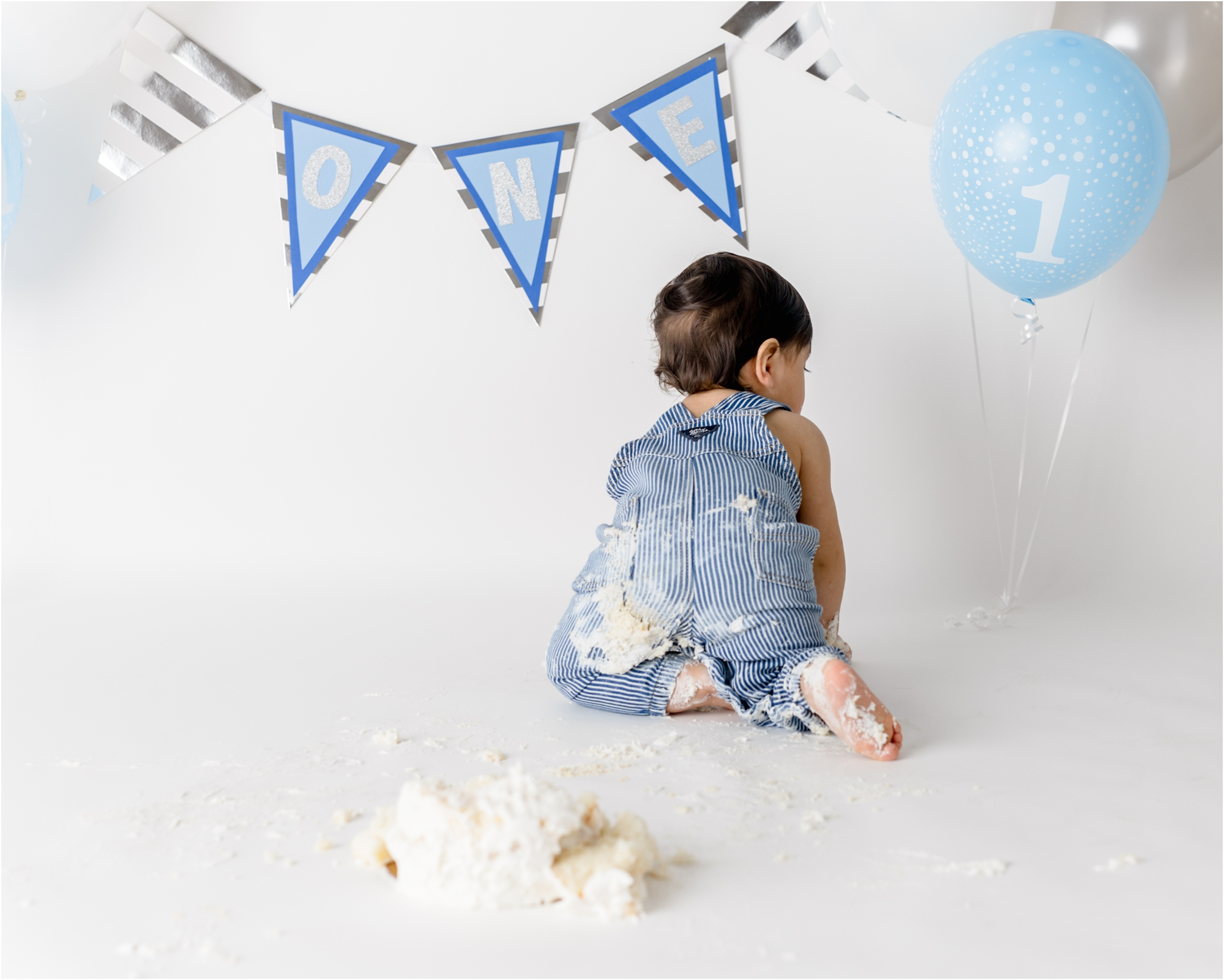 Baby crawling away from cake smash during in studio session. Photo by Lifetime of Clicks Photography.