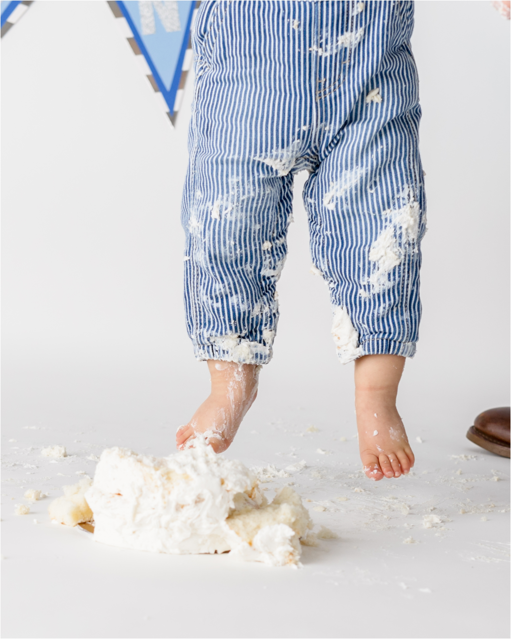 Closeup of baby's feet near cake after first birthday cake smash session in Houston studio. Photo by Lifetime of Clicks Photography.