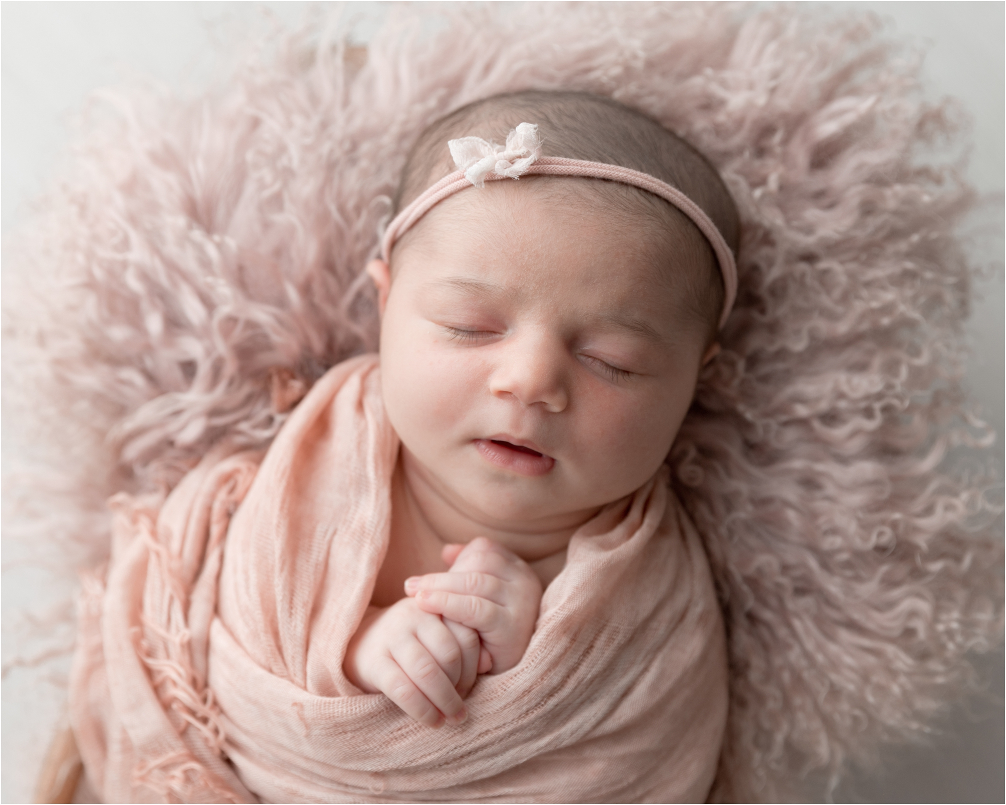 Closeup of sleeping baby with blush props. Photo by Lifetime of Clicks Photography.