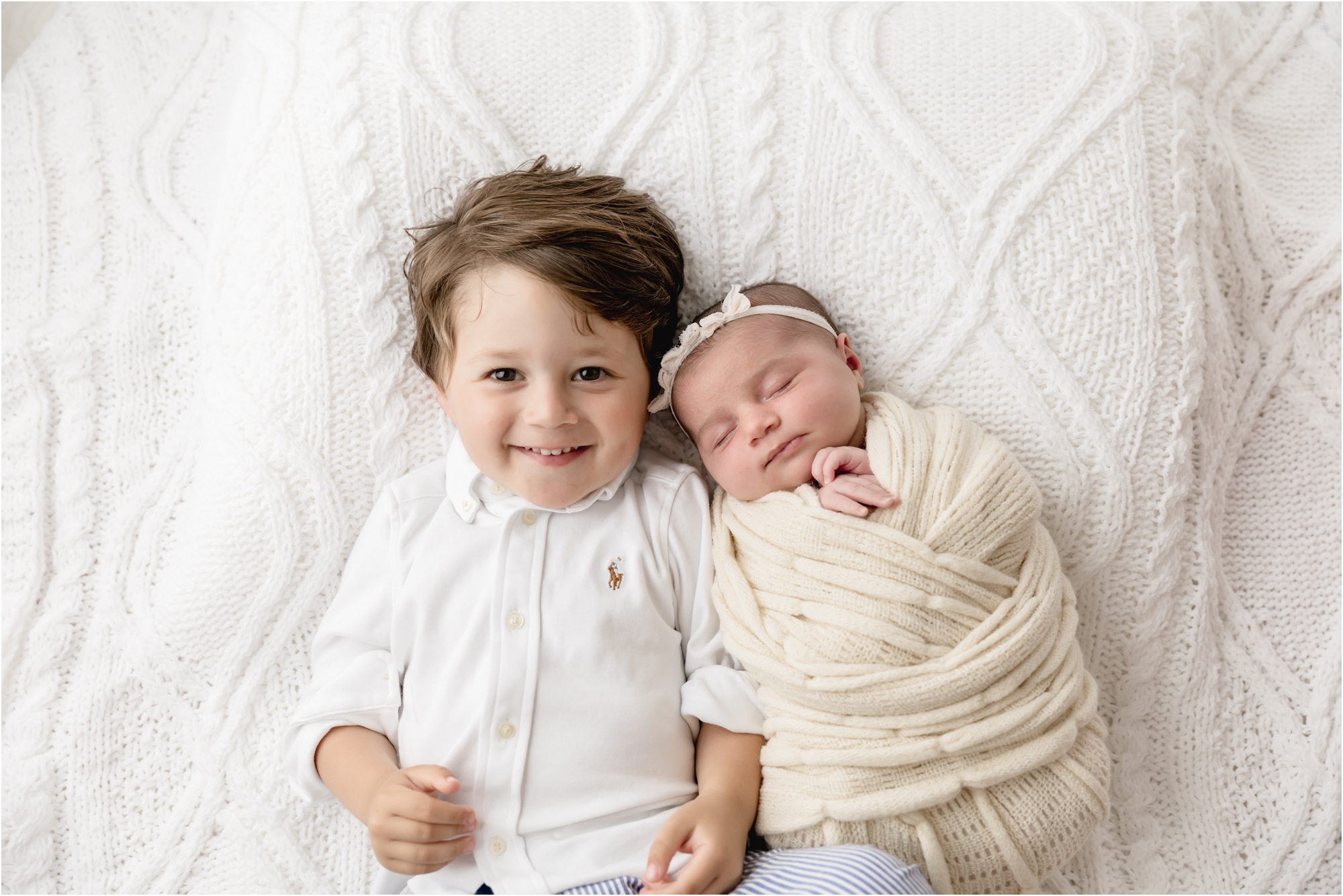 Brother smiling at camera next to newborn baby sister. Photo by Lifetime of Clicks Photography.