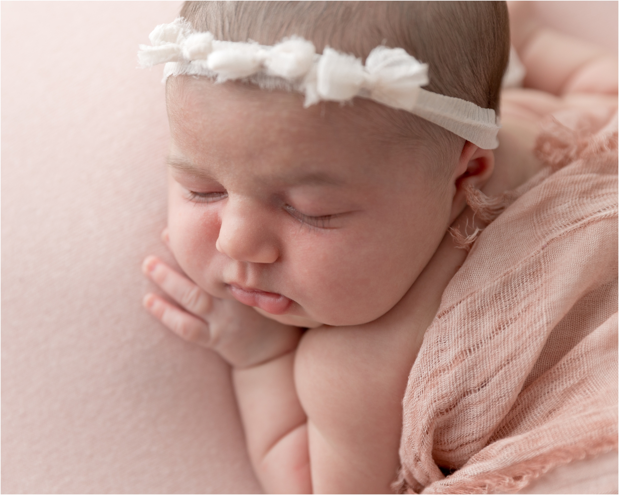 Newborn sleeping on pink backdrop with pink gauze wrap. Photo by Lifetime of Clicks Photography.