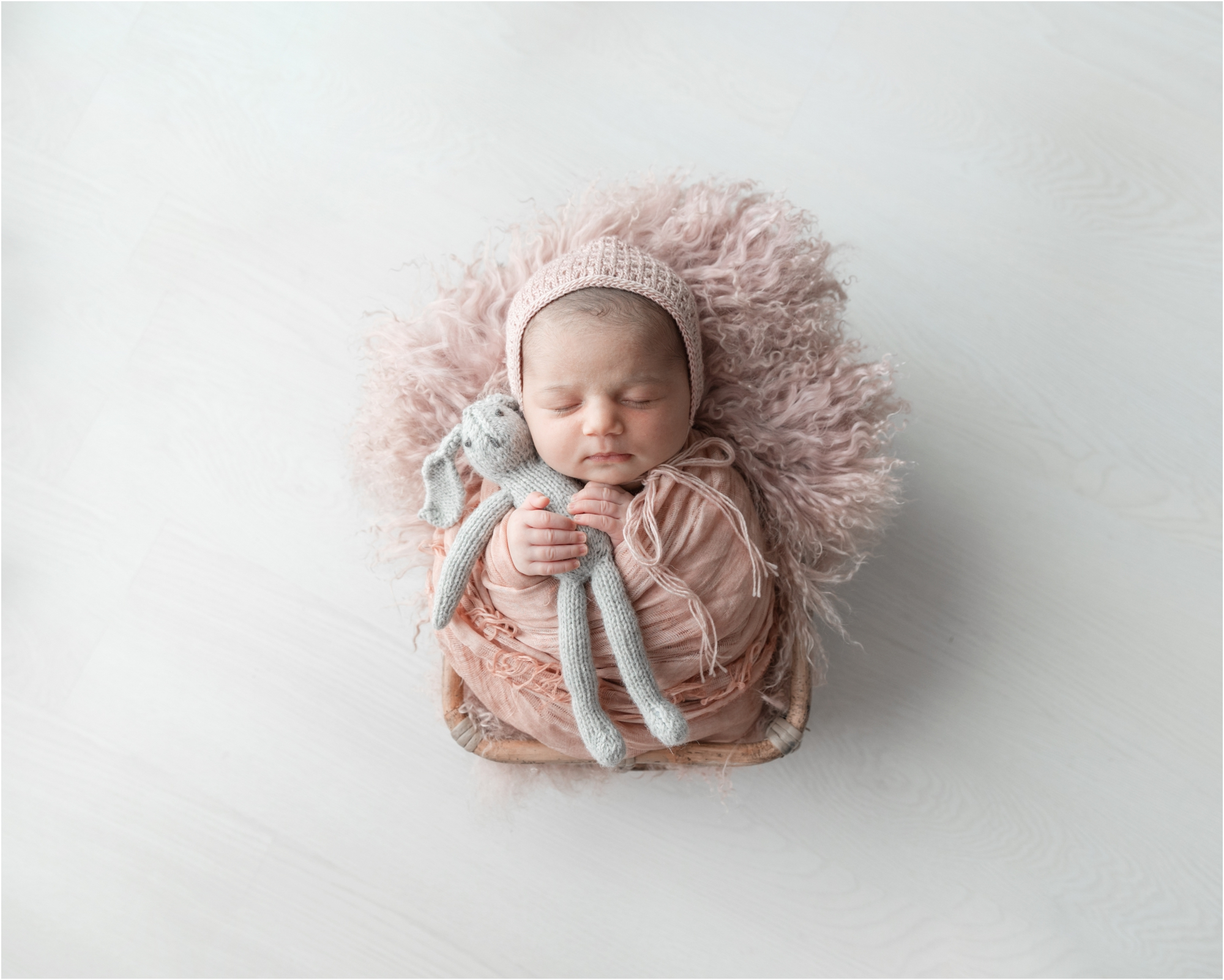 Baby girl in pink bonnet hugging knit stuffed animal. Photo by Lifetime of Clicks Photography.