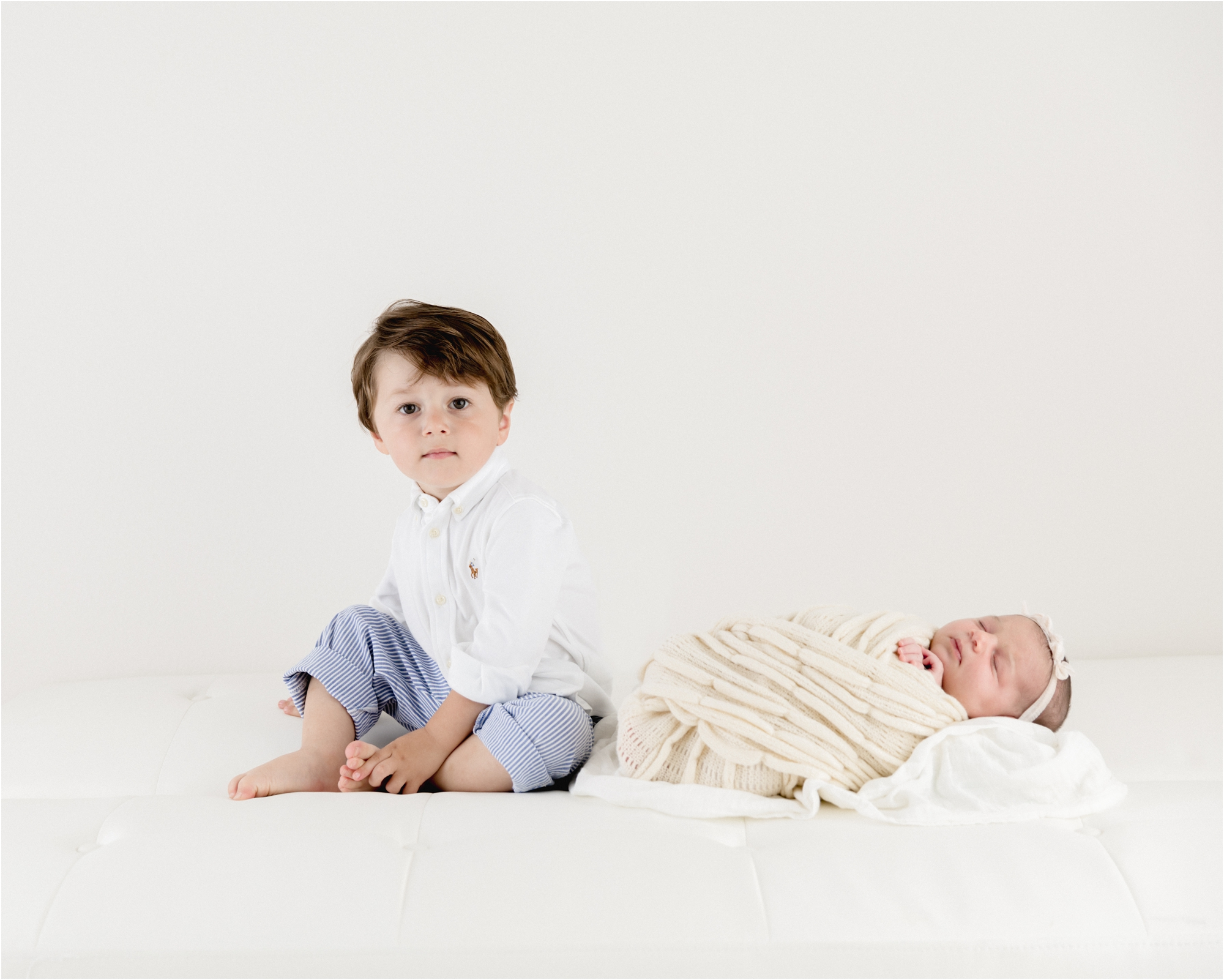 Big brother sitting on bed next to baby sister. Photo by Lifetime of Clicks Photography.